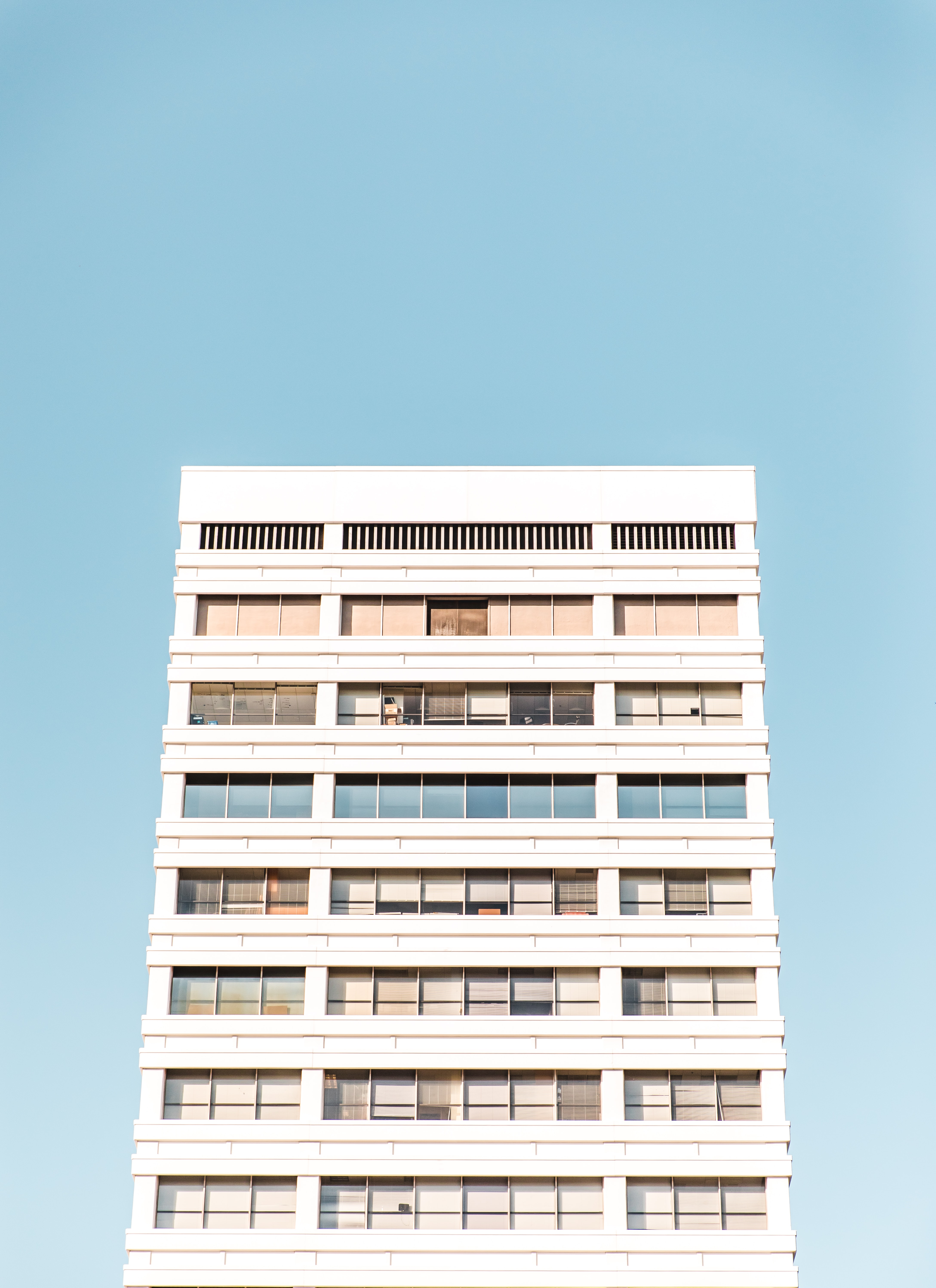 A white residential building against a pale blue sky