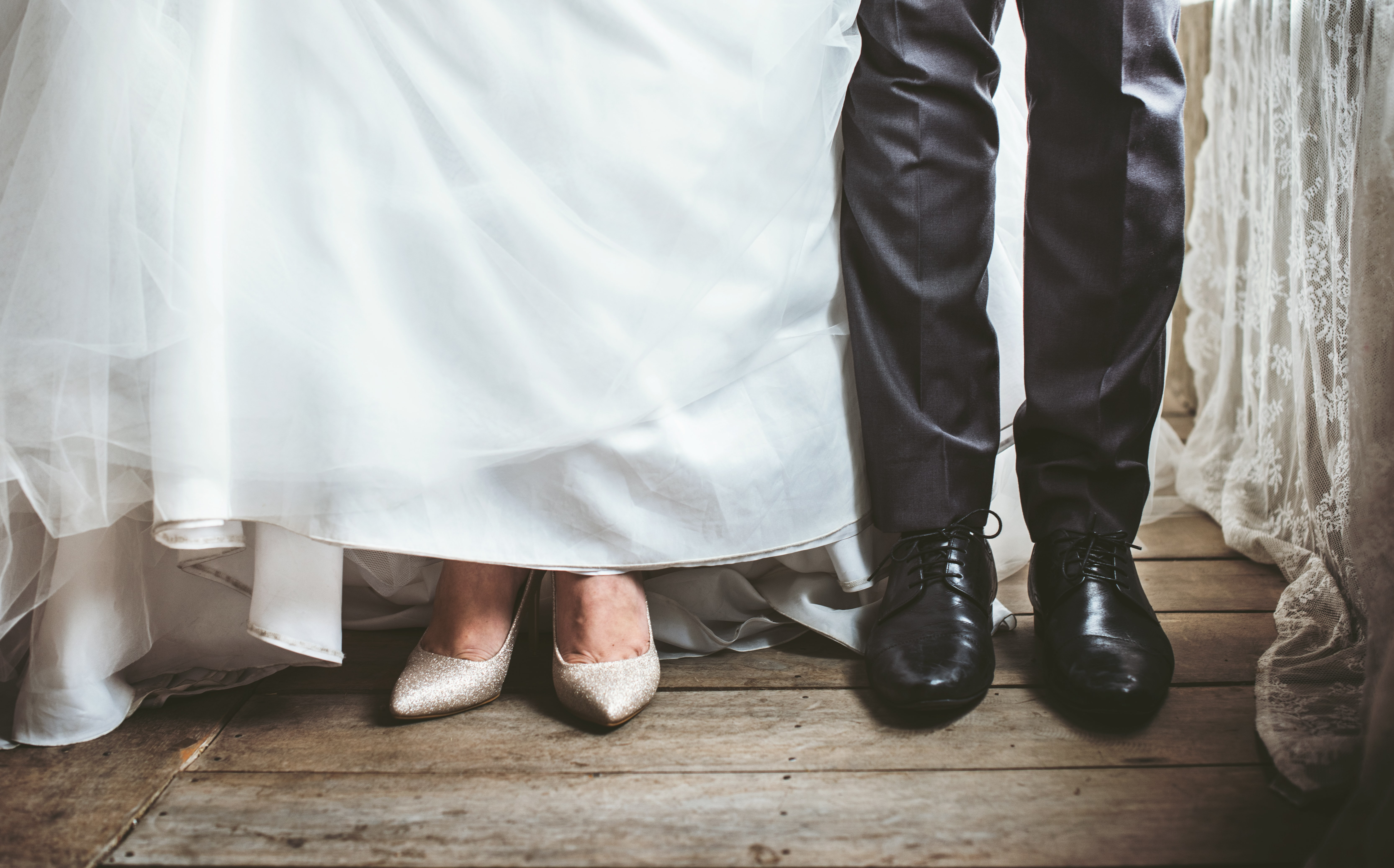 A bride and groom's feet in a white dress and black suit