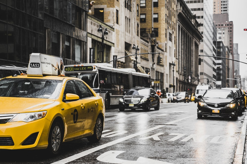 yellow taxi travelling on city streets