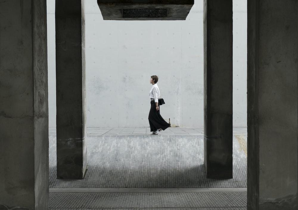 woman walking under a concrete bridge during daytime