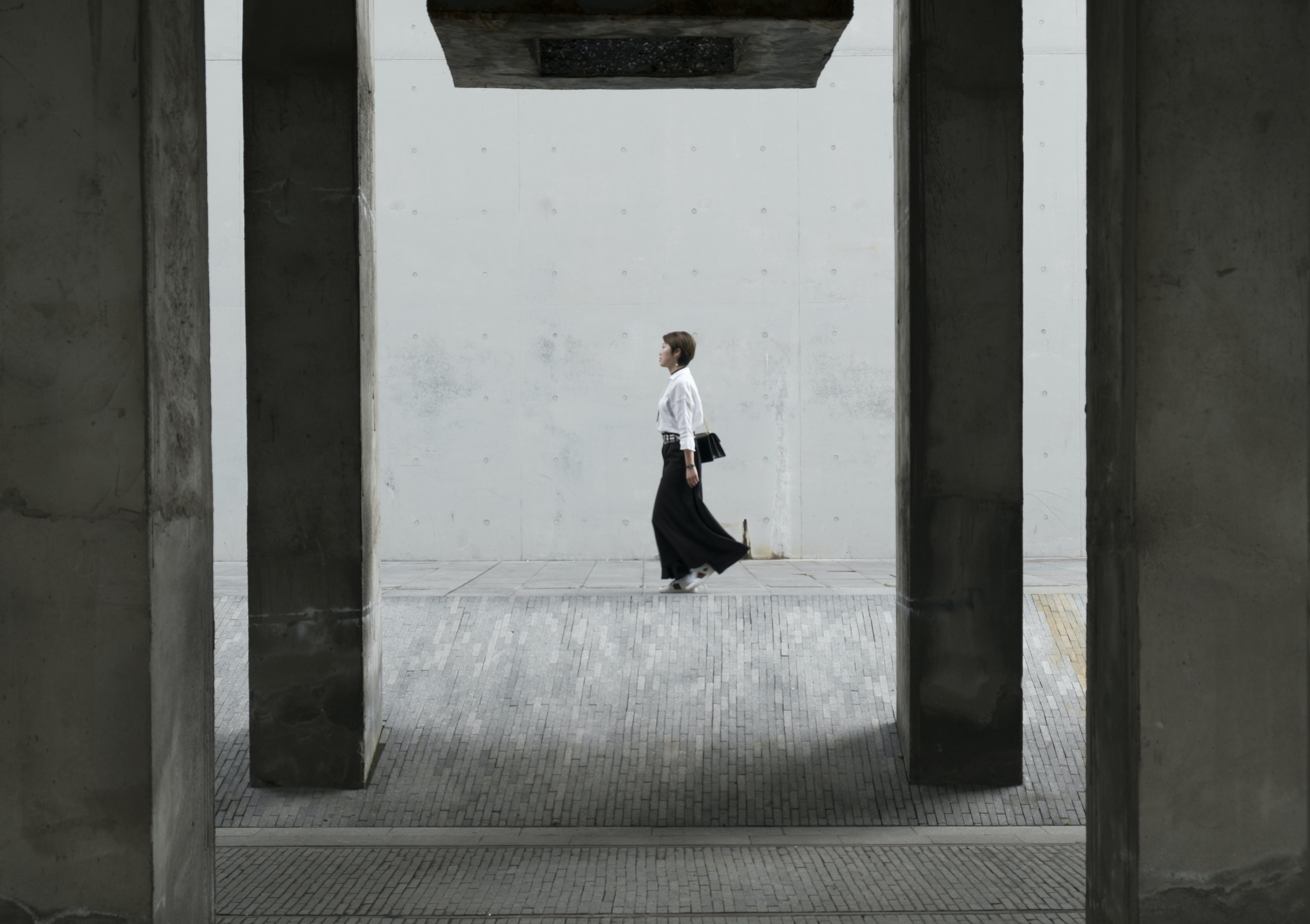 A woman in a black skirt walking on a sidewalk near a wall