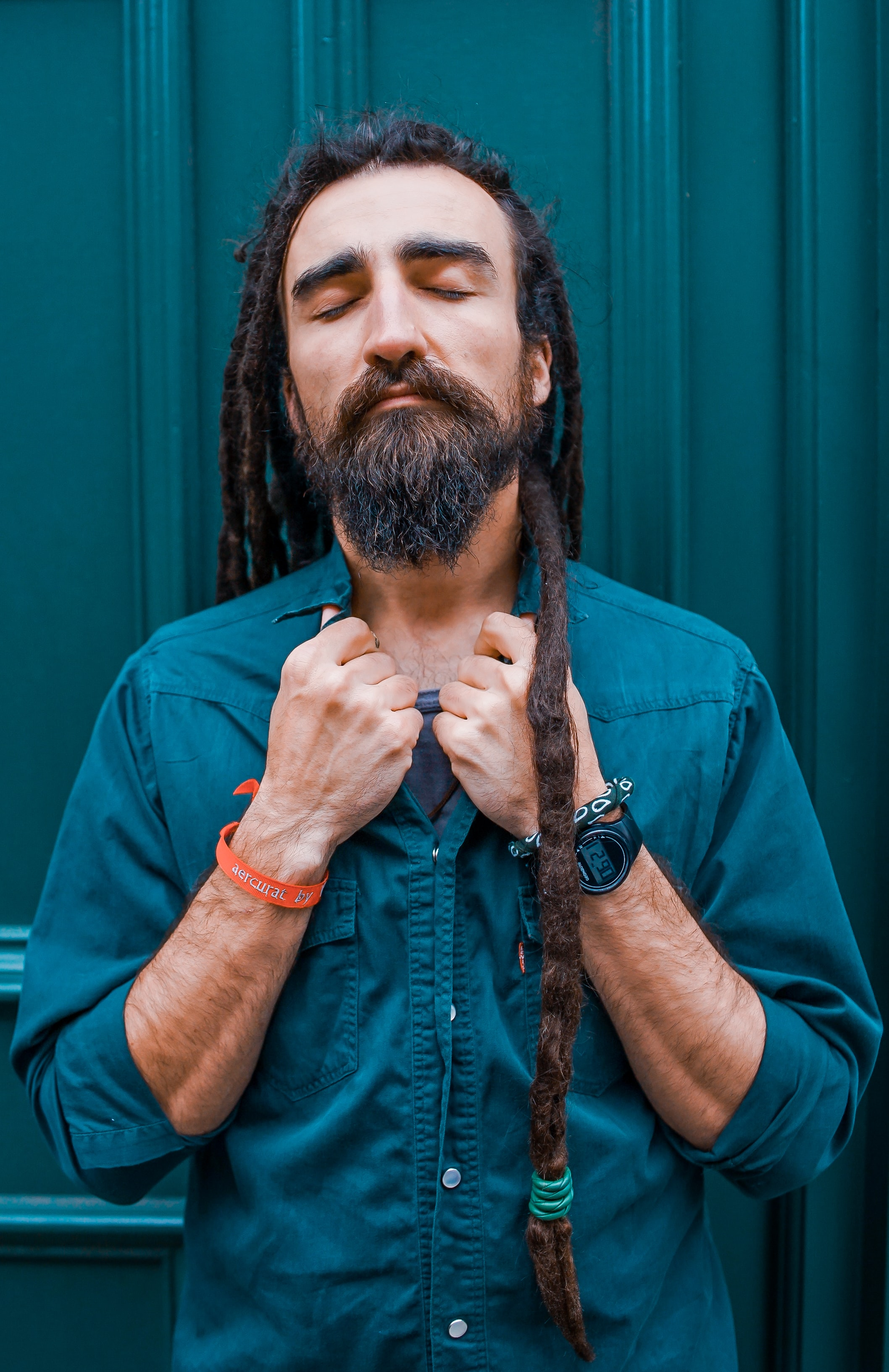 Older man with beard and dreadlocks closes his eye peacefully