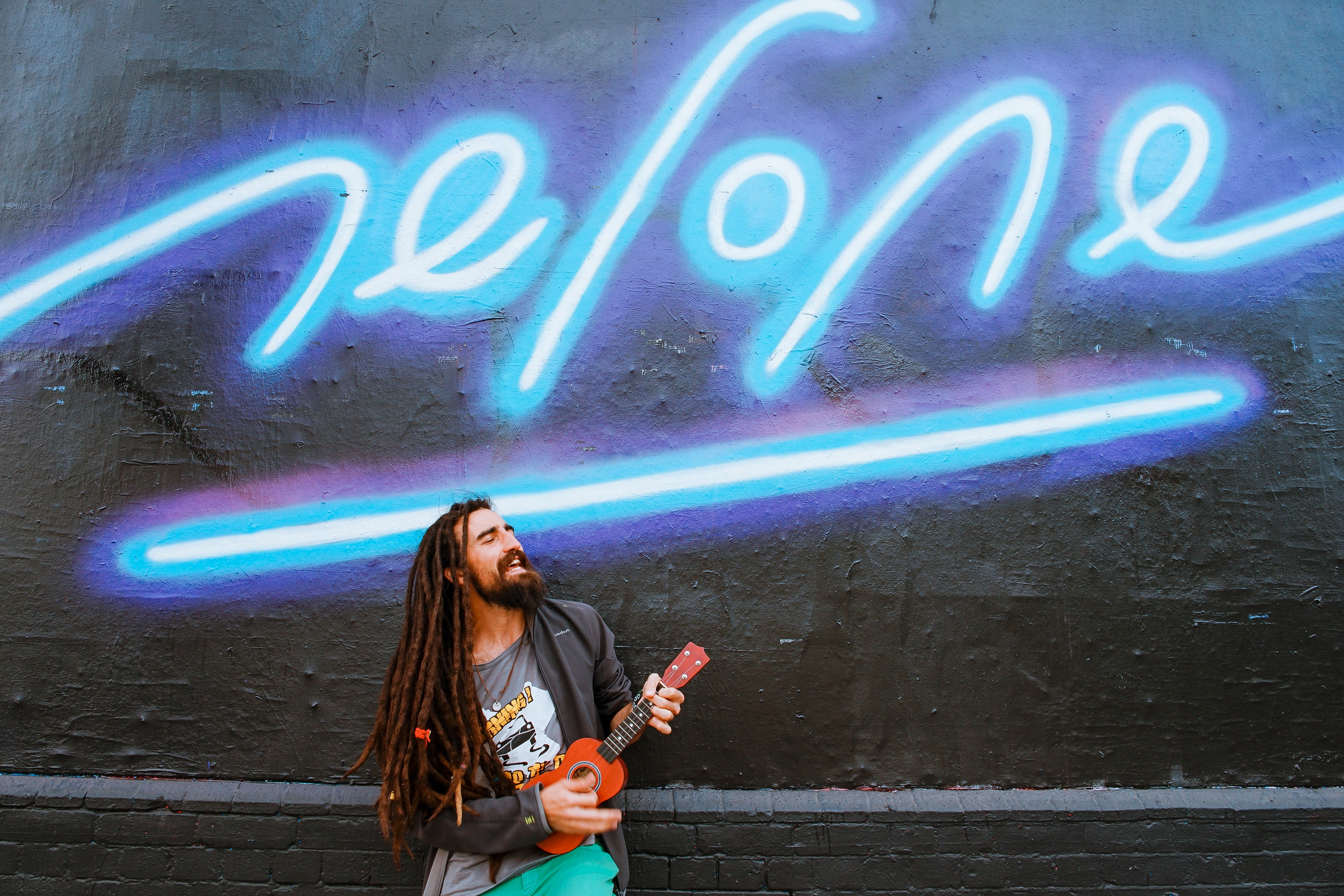 Bright blue graffiti typography on wall with man in dreadlocks performing on red ukulele in London
