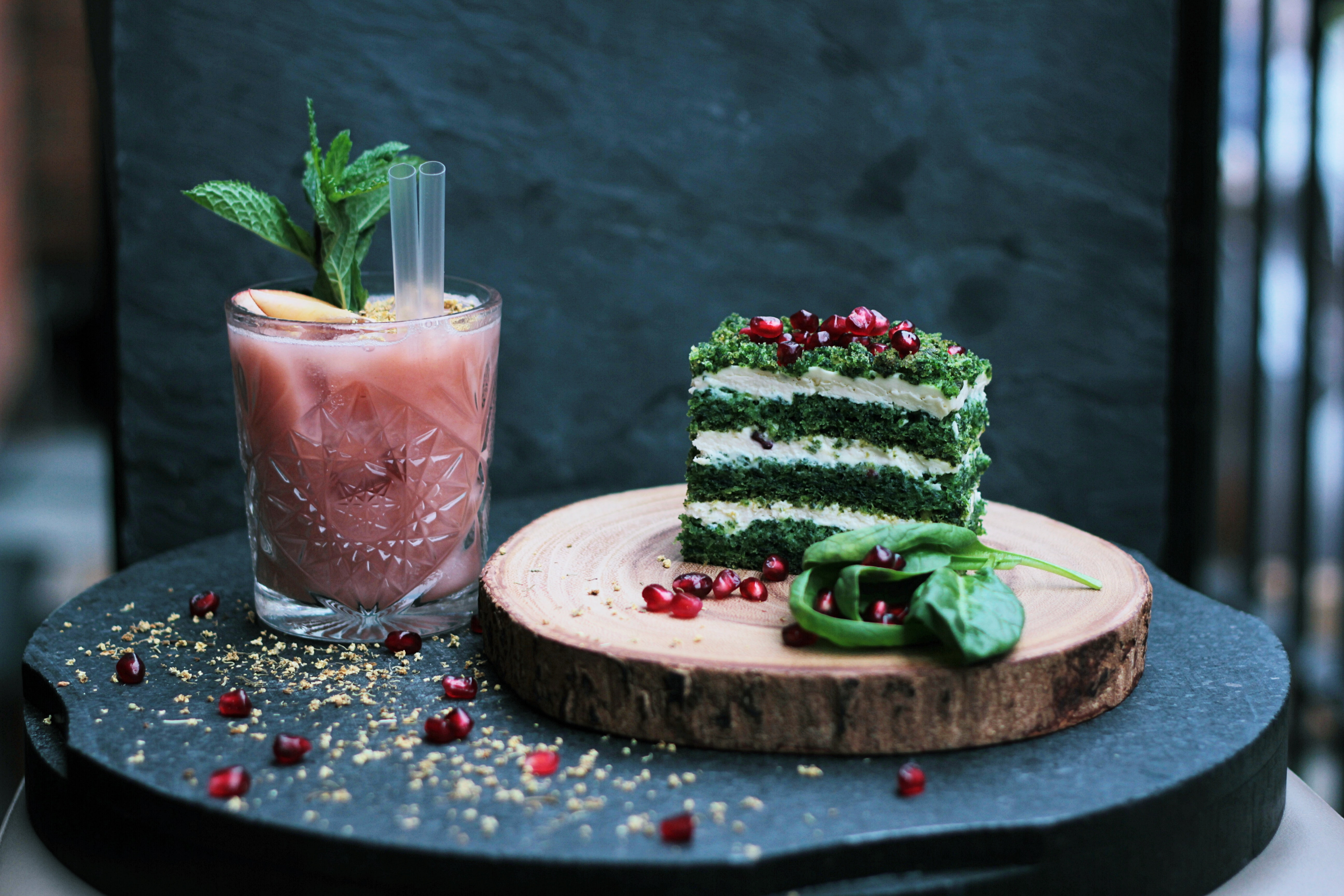 Photo of a red smoothie or juice and a green layered slice of cake, decorated with pomegranate seeds