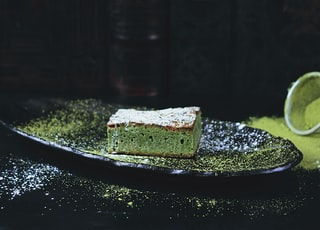 green and brown sponge cake on black oval plate