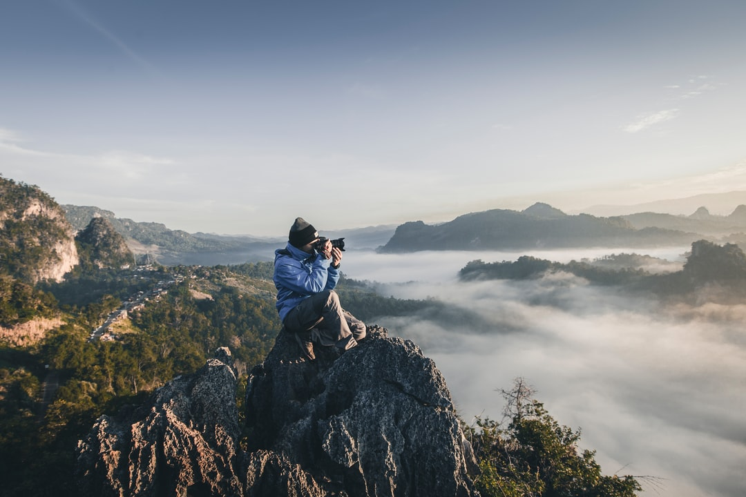 A man with a long-lens camera sitting on top of jagged rocks overlooking wooded hills