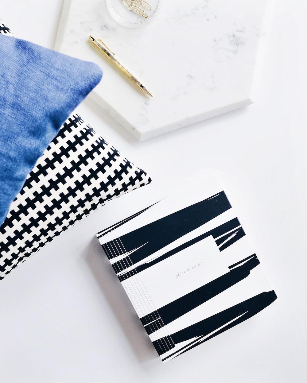 gray retractable pen beside blue textile