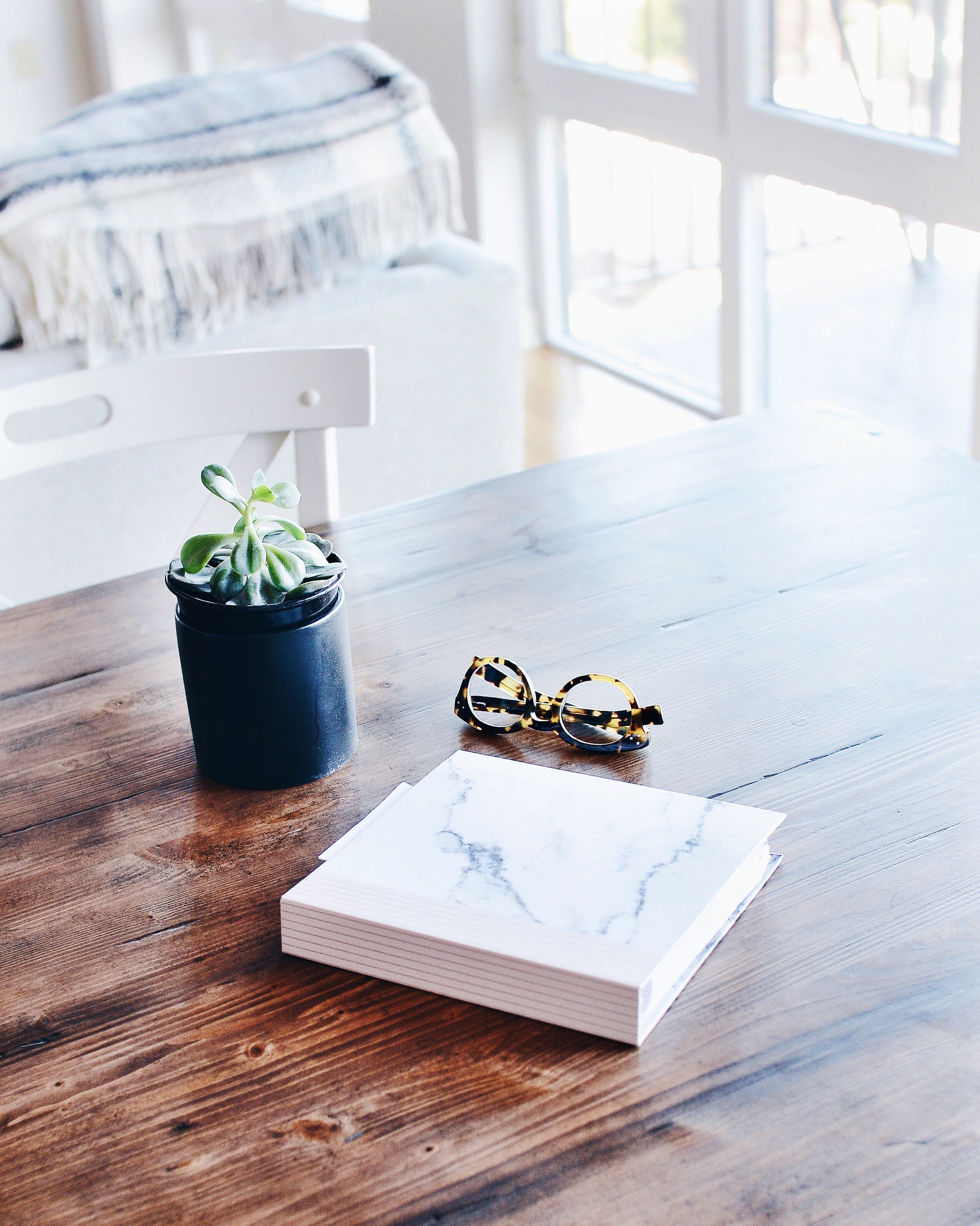 A potted plant, an album and a pair of glasses on a wooden table in a bright interior