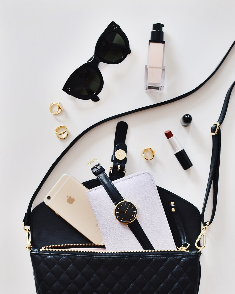women's sunglasses and black bag with watch and iPhone 6