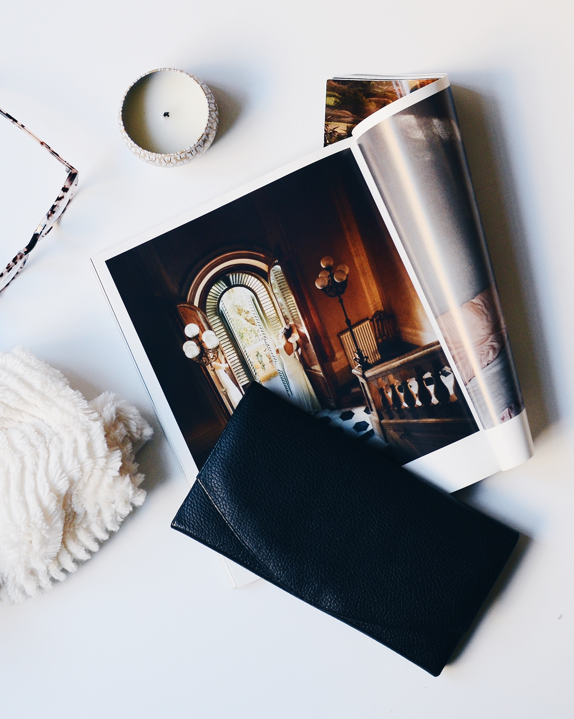 A flatlay with a magazine with large photographs, a purse and a candle