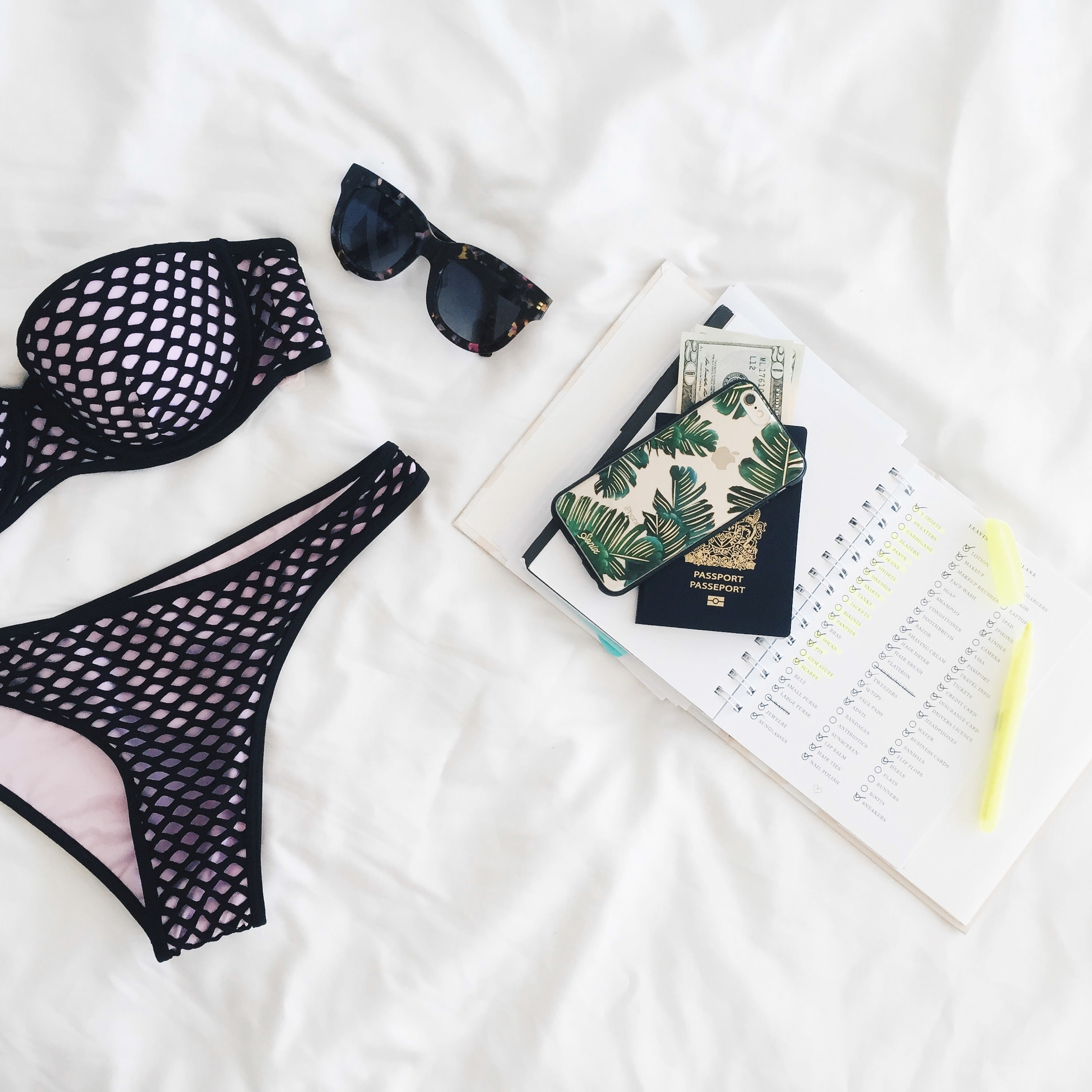 A flatlay with a notebook, a phone, a passport, sunglasses and a bikini