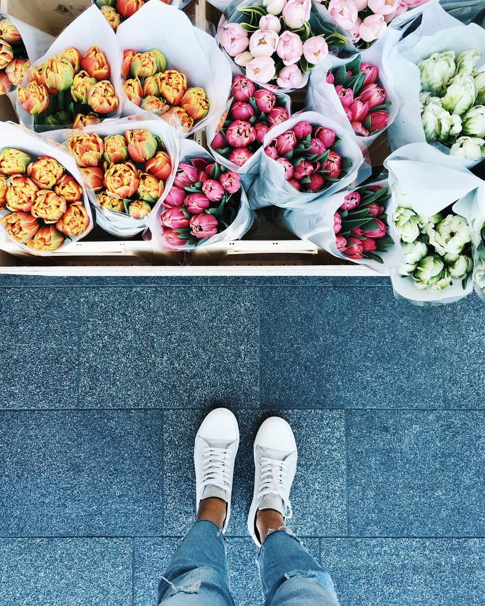 A person looking down at various flower bouquets.