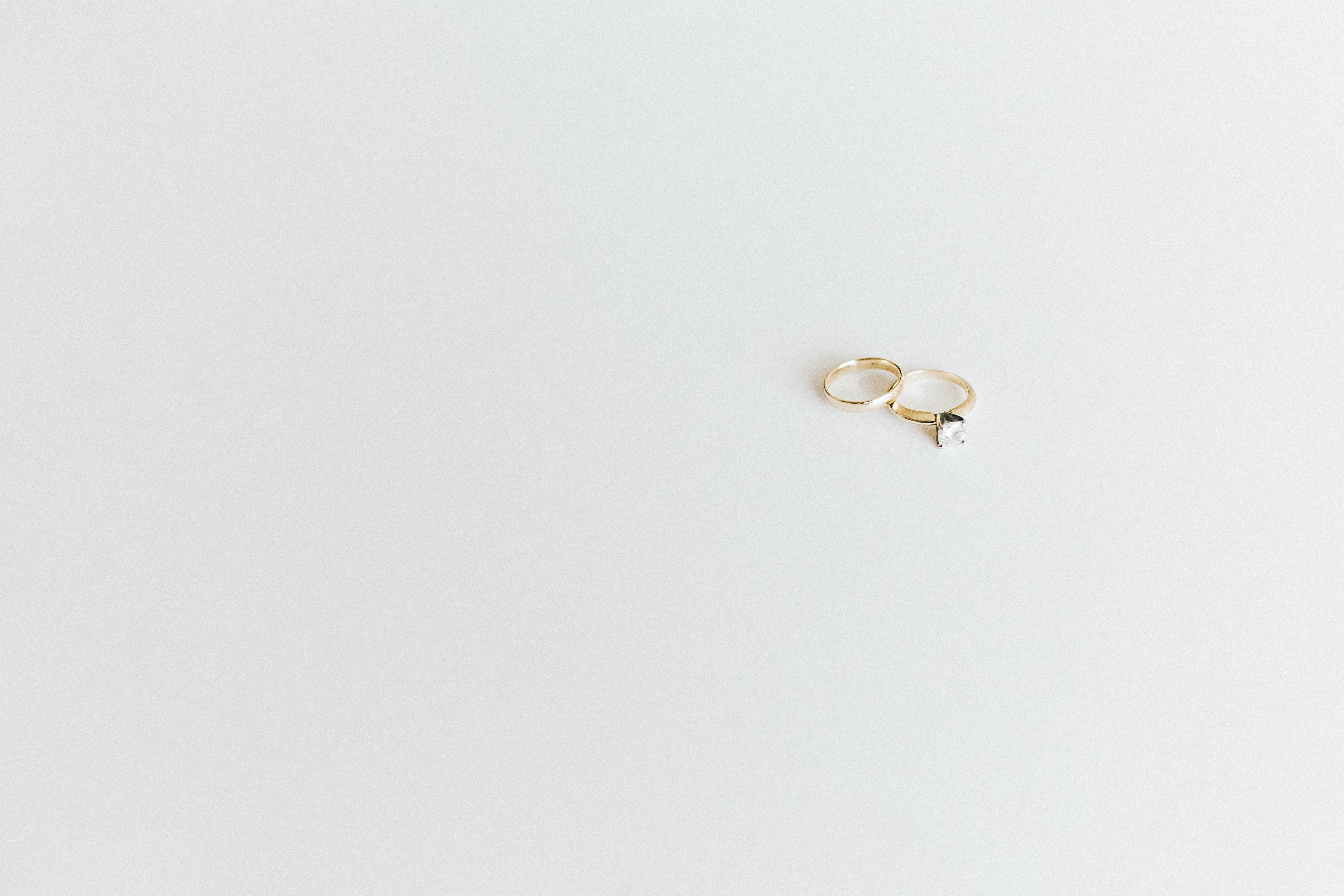 Delicate gold wedding rings sit on a minimalist white surface