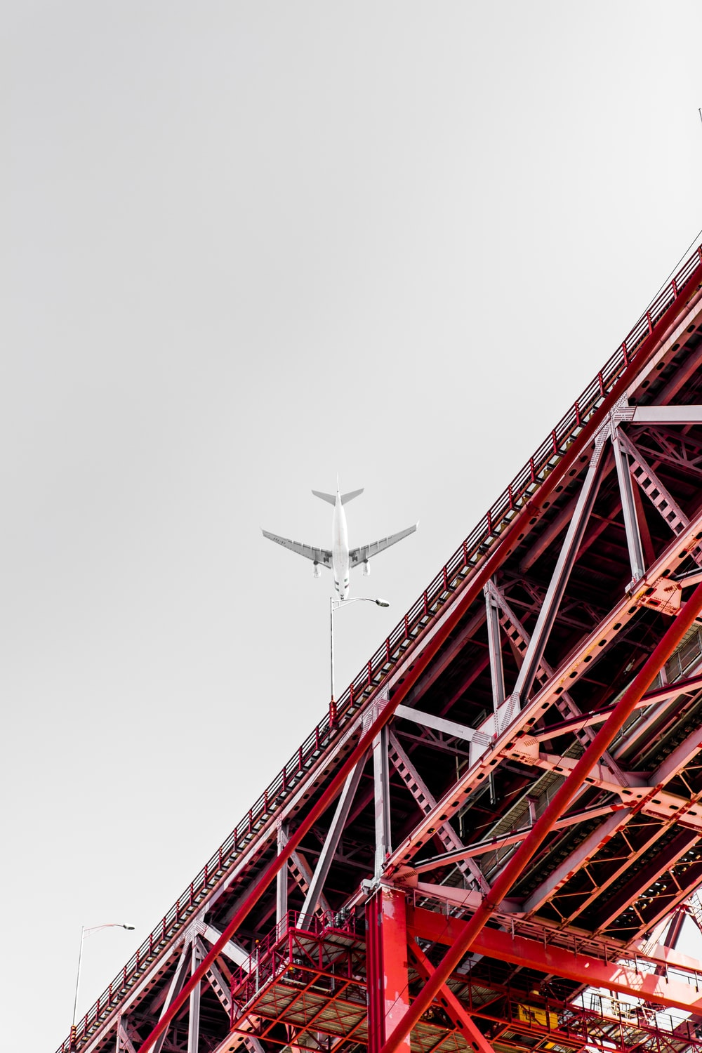 low angle photography of transportation plane above the bridge