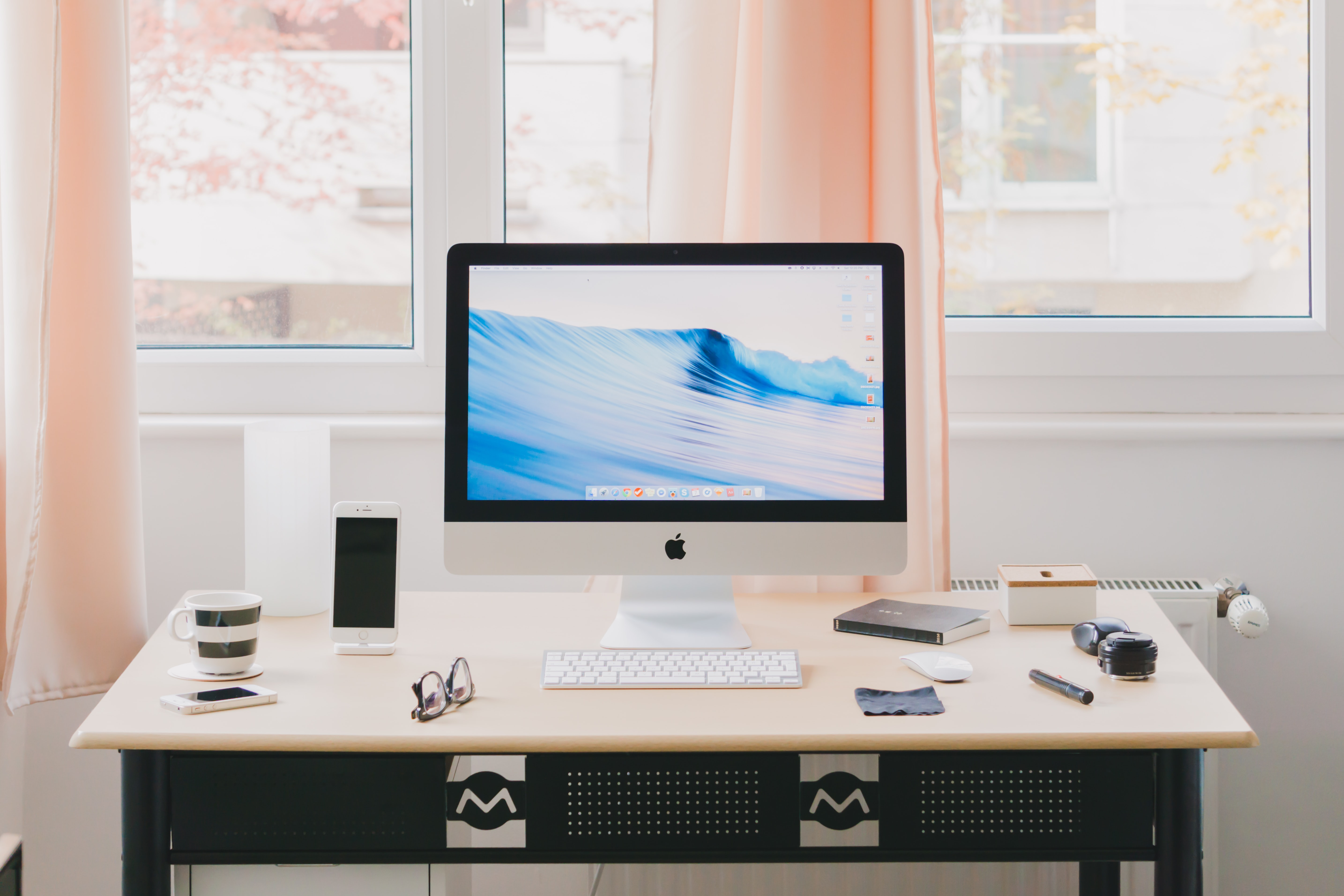 A desk with an iMac computer, a coffee cup and various accessories