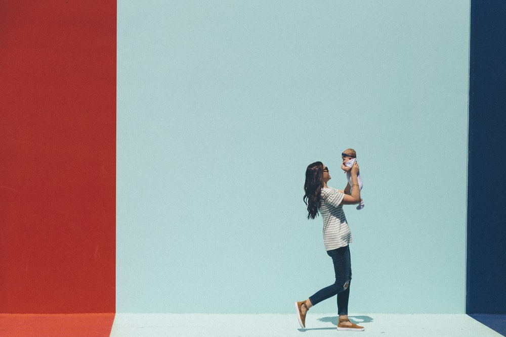 woman carrying baby while walking