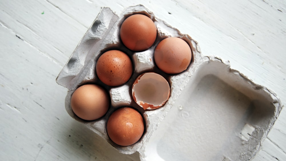 five whole eggs and one empty half-open egg inside open egg tray