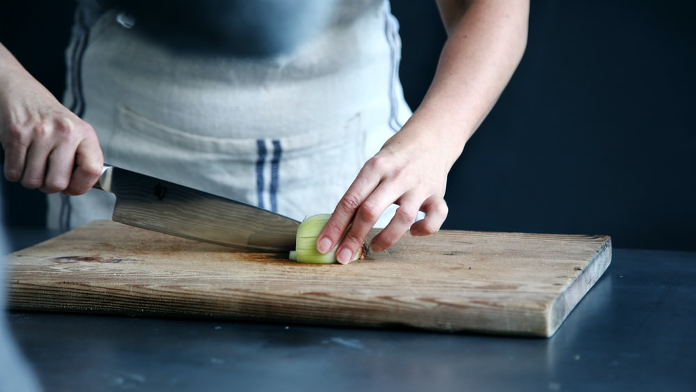 person slicing green vegetable on chopping board
