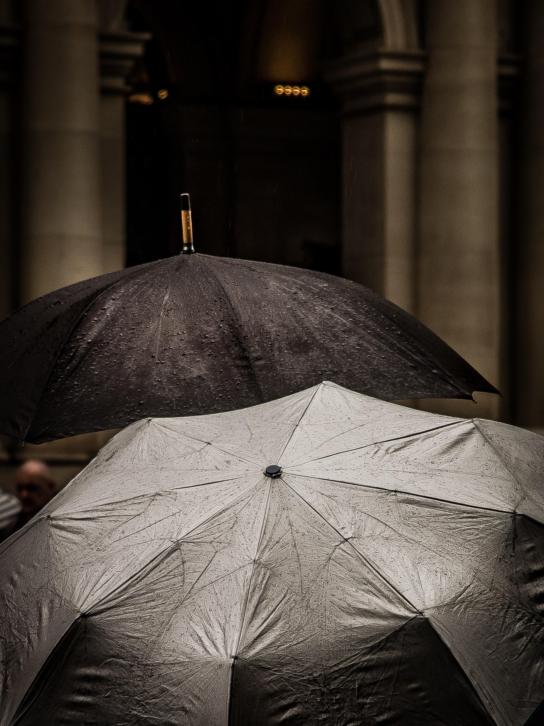 A black and a silver reflective umbrella during the rain on Bourke Street