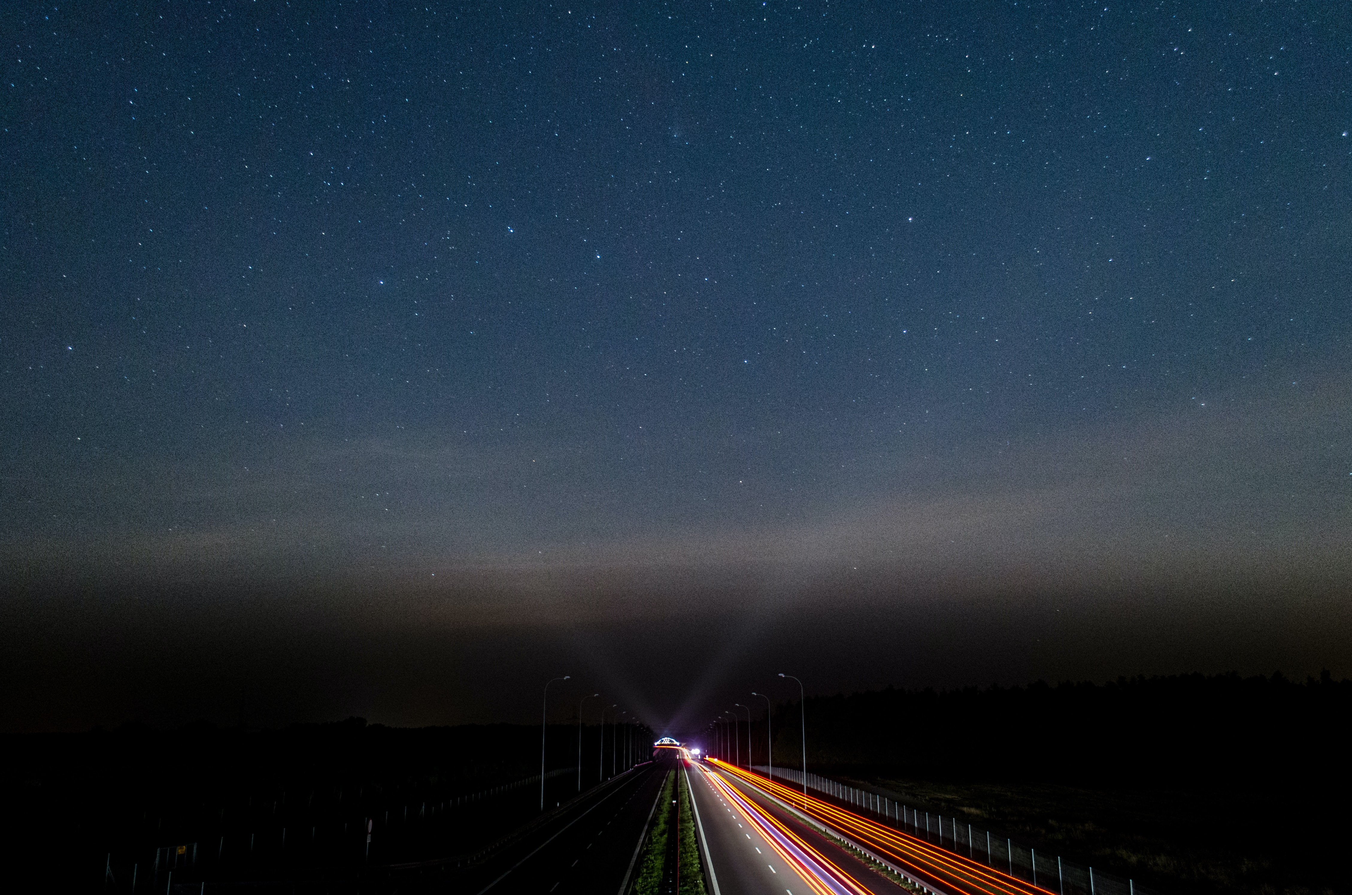A drone's perspective of the starlit night sky, with lights reflecting from the traffic below