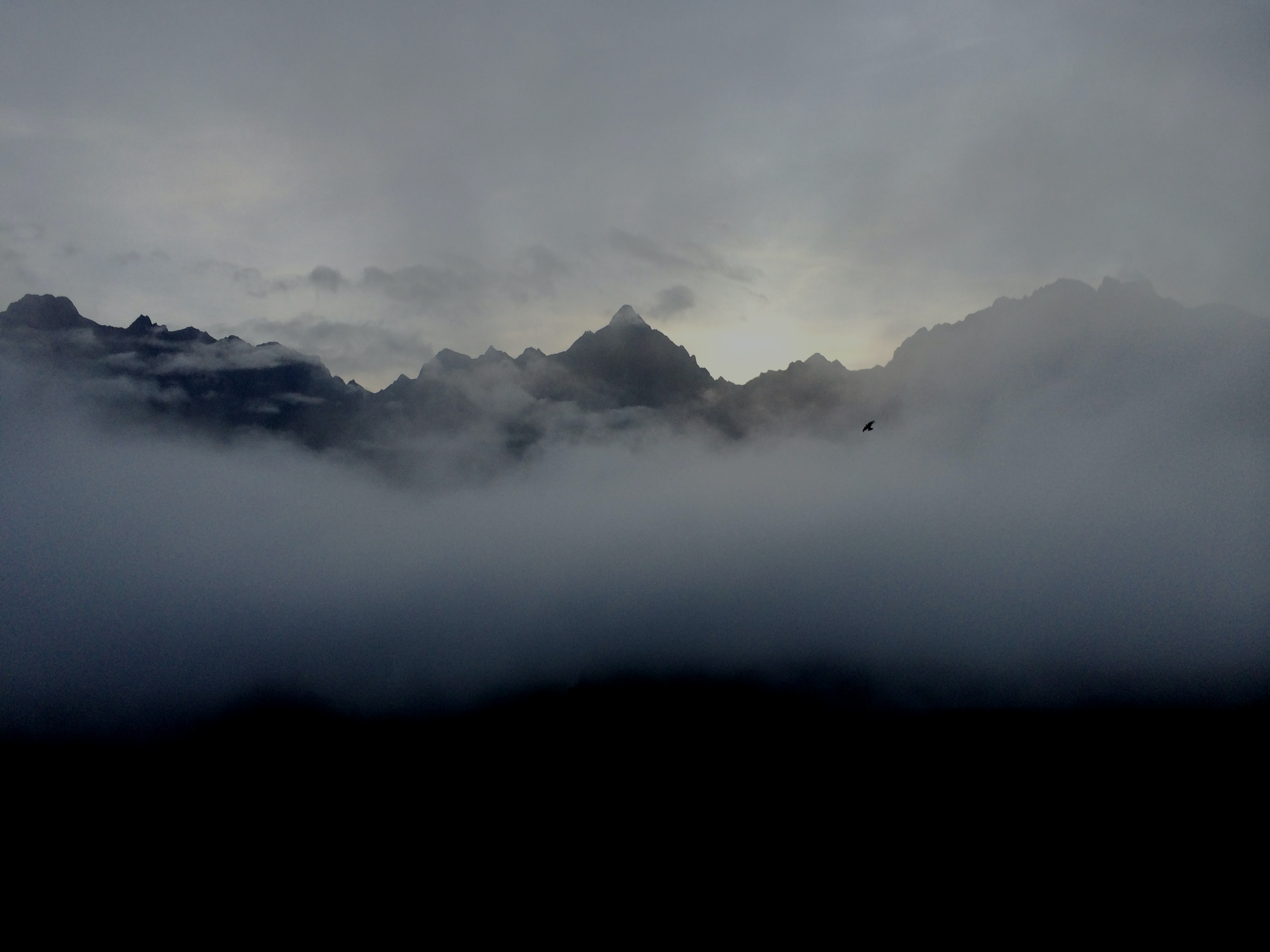 Thick clouds framing the silhouette of a sharp mountain ridge