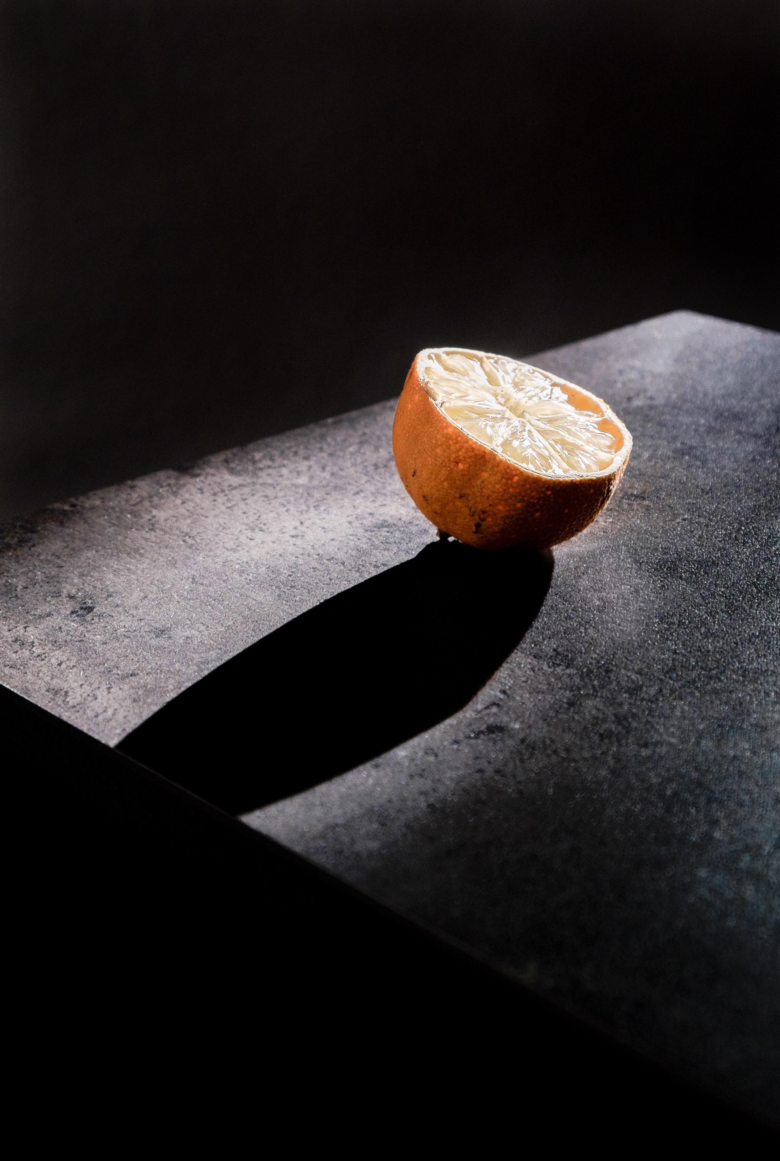 A half of a lemon casting a long shadow on a black surface
