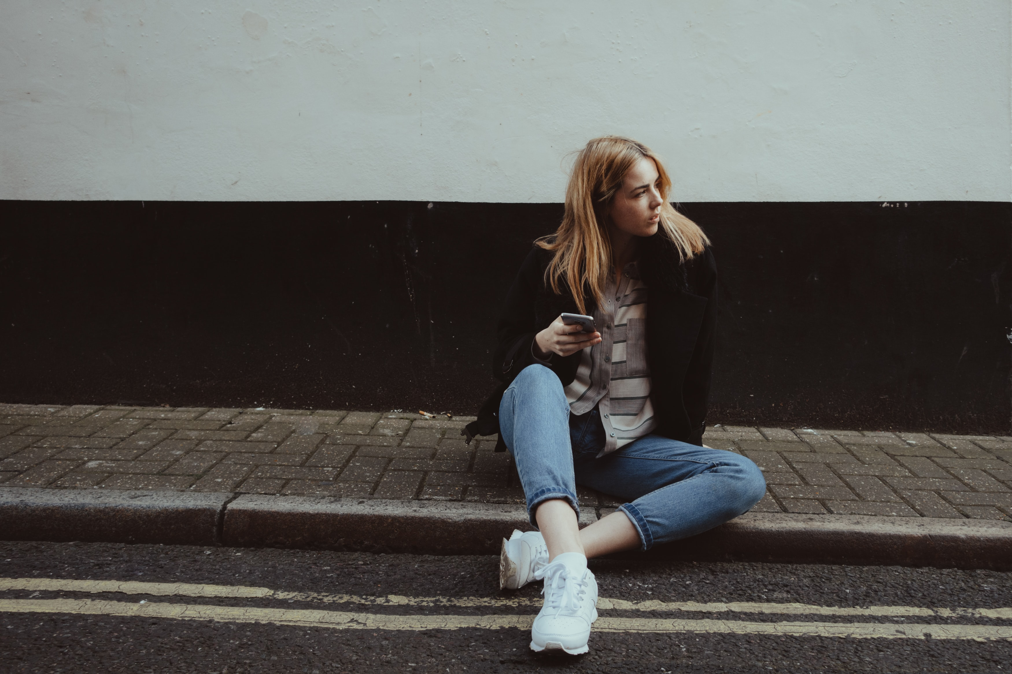 A blonde woman wearing a black jacket sitting on the curb in Marylebone