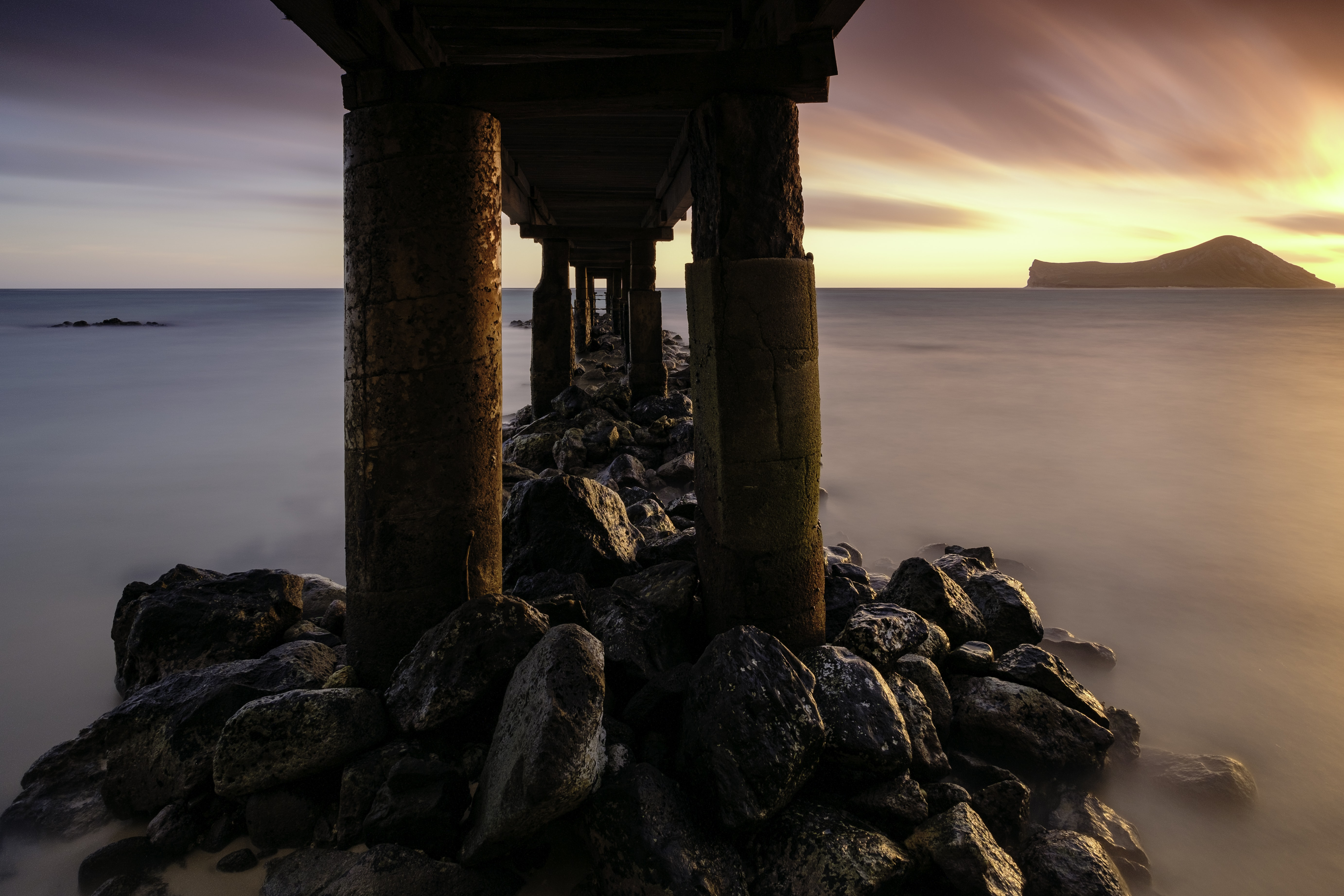 An underneath view of a bridge and rocks over the sea with the sunset in the background