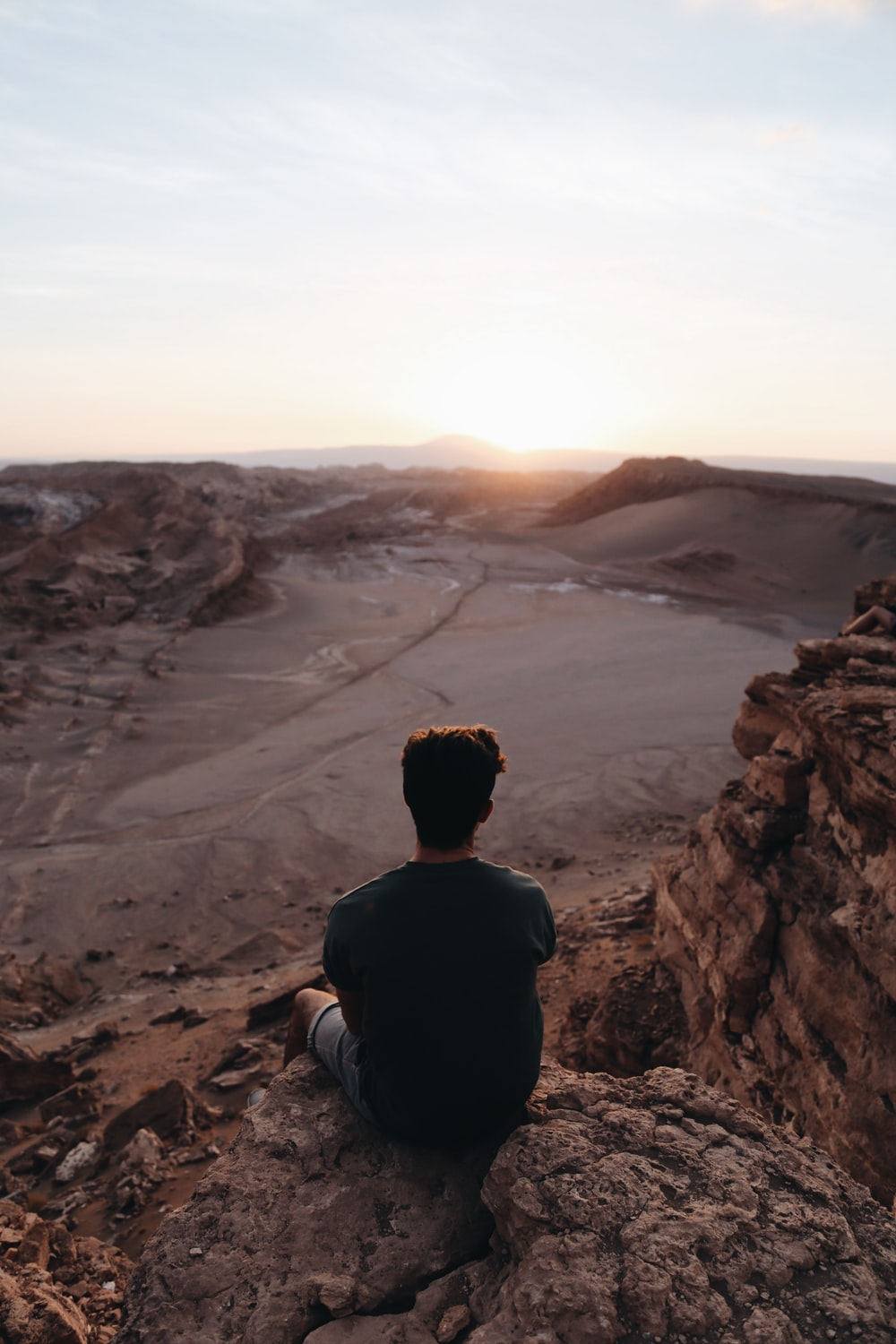 man sitting on cliff facing open field during daytime