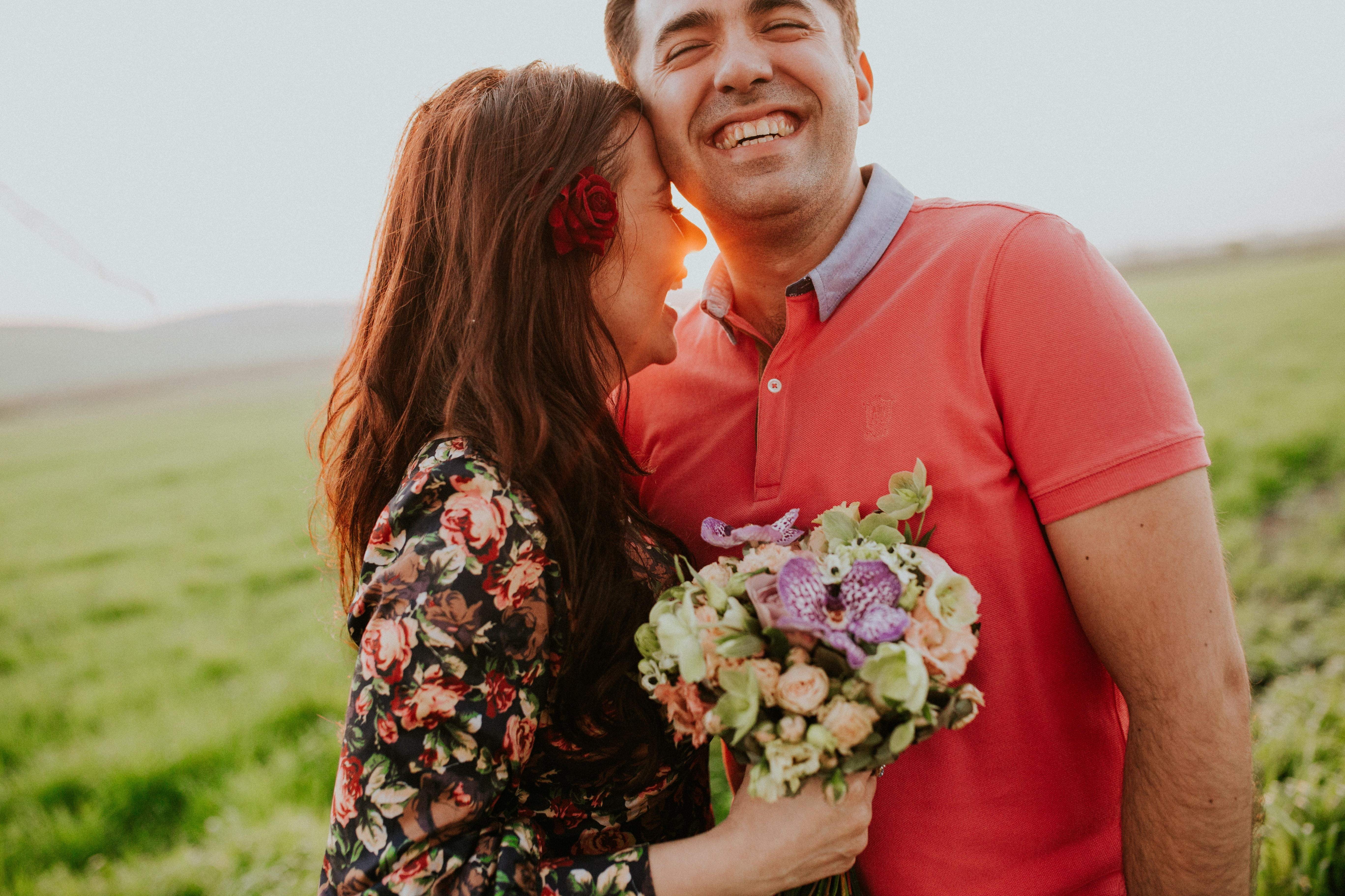 A man and a woman laughing in a sunny field. She holds a bouquet of flowers.