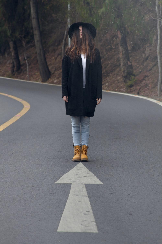 woman standing on asphalt road