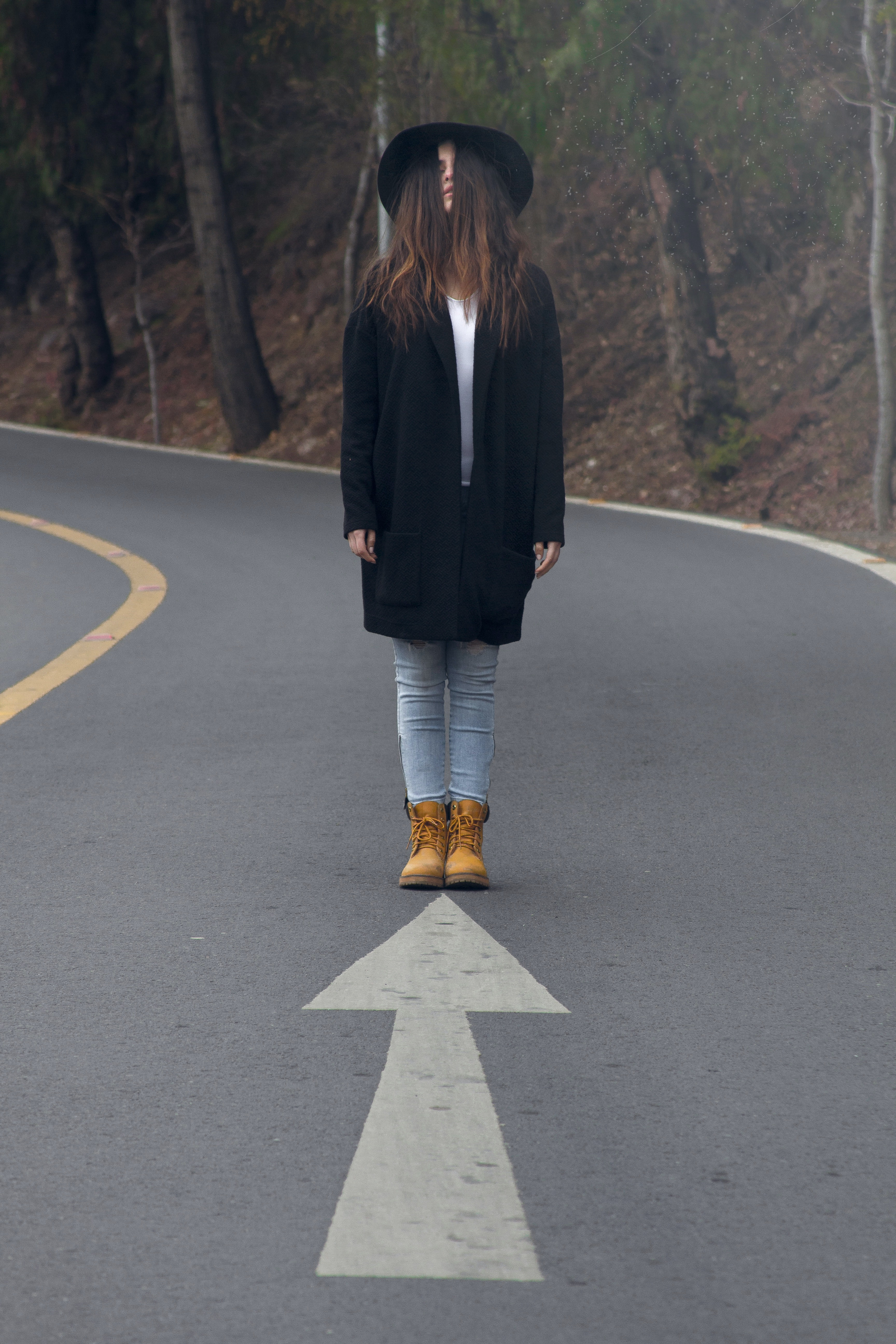 A woman with hair covering her face stands on a road, a painted arrow facing her