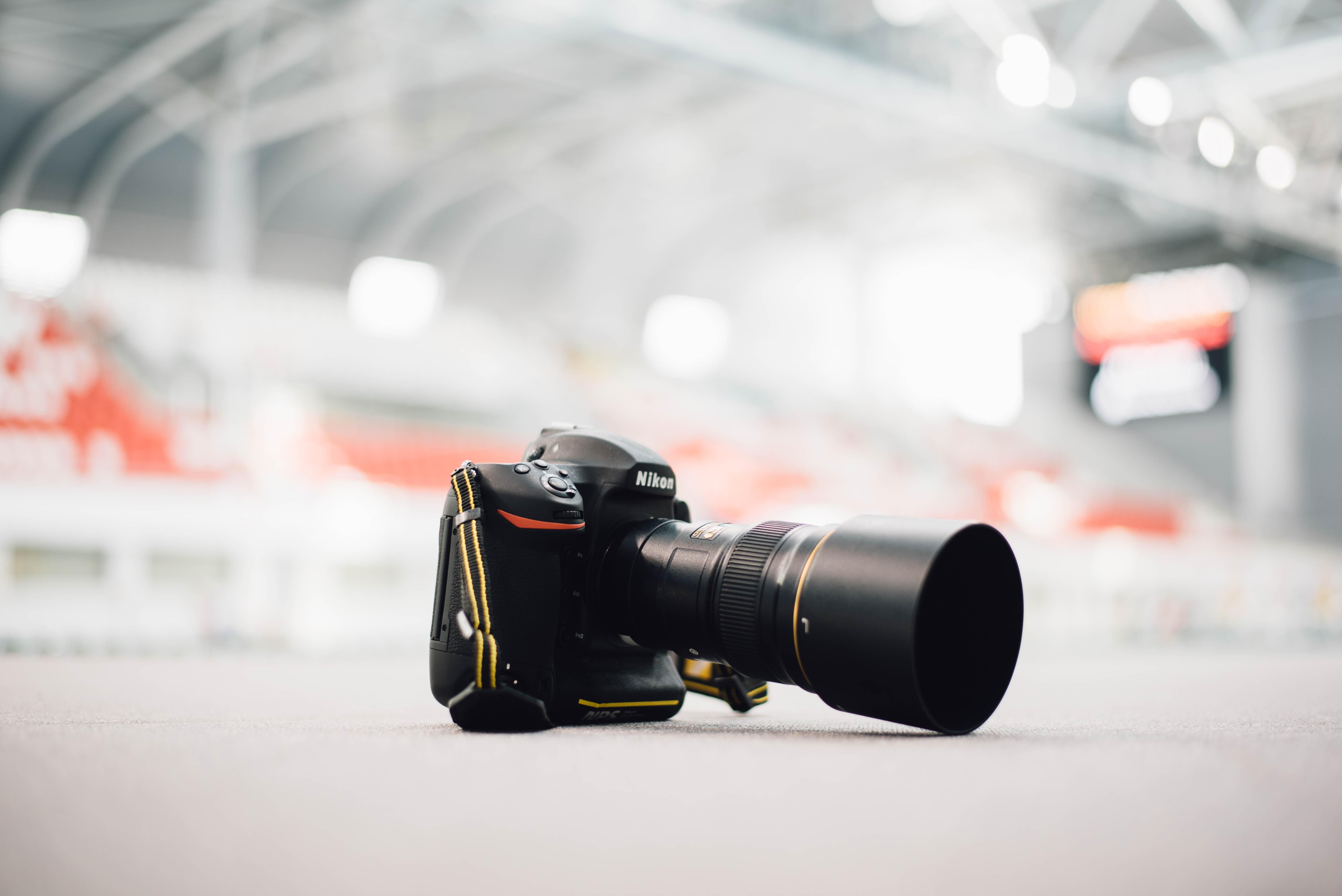 selective focus photography of Nikon DSLR camera on ground