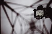 person holding DSLR camera capturing bridge