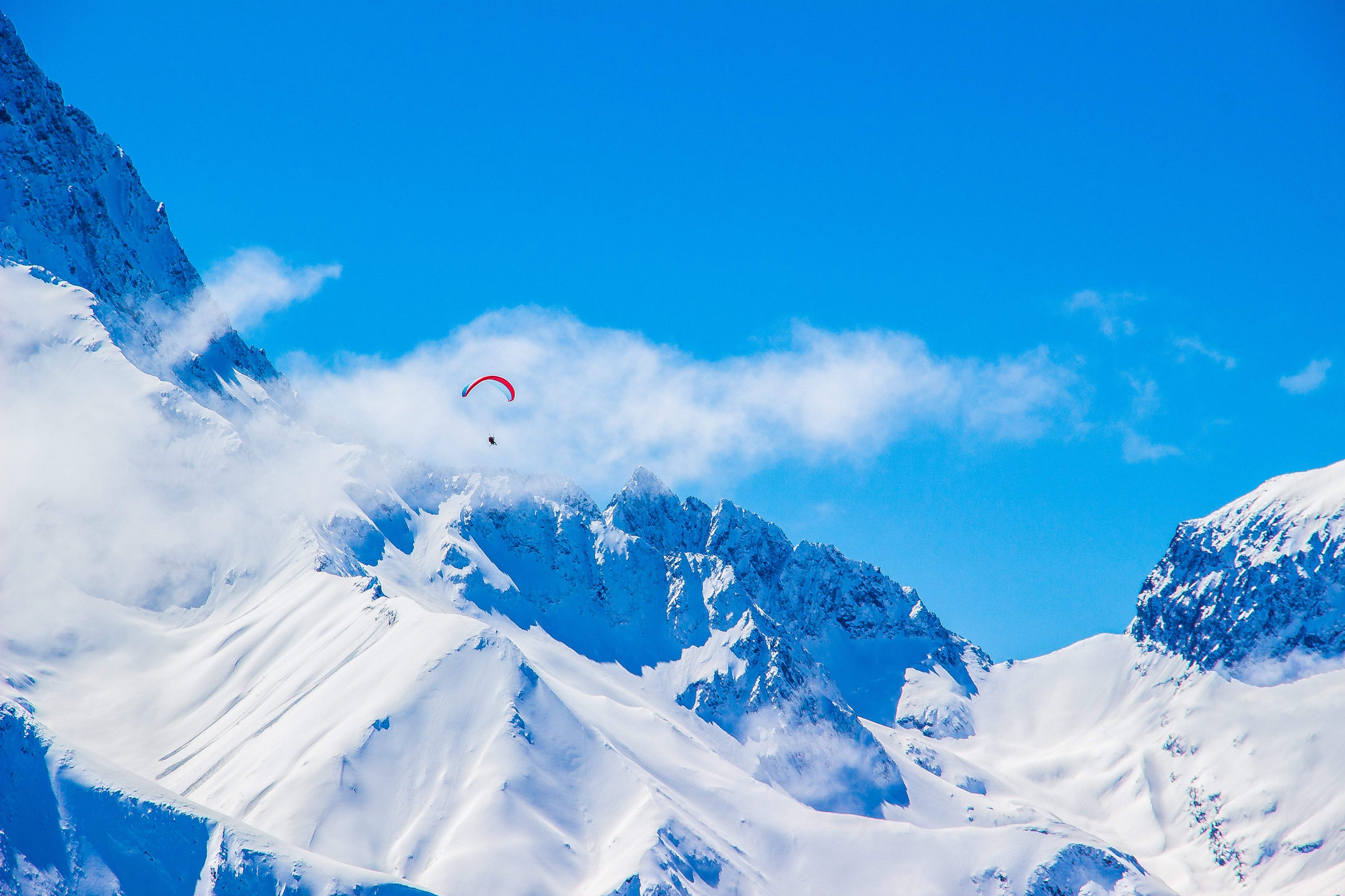 photo of person with parachute above snowy mountain