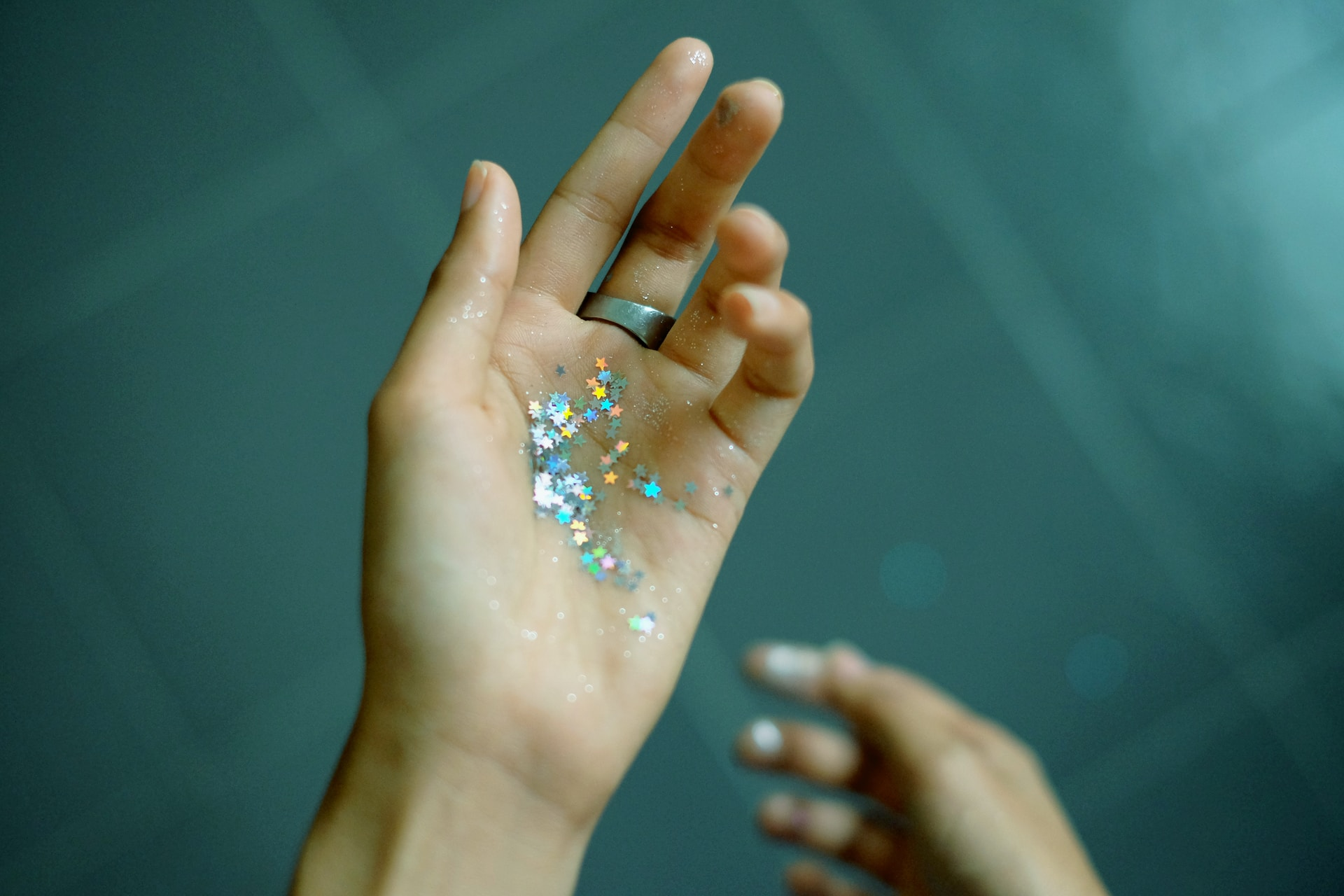 person showing hands with glitters