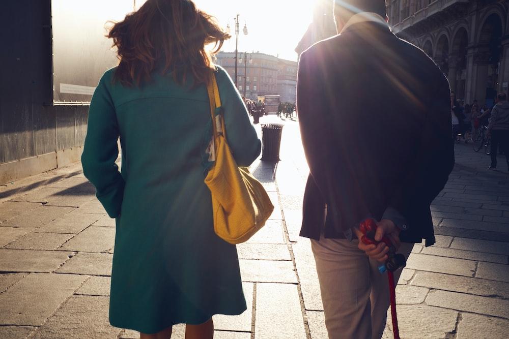woman and man walking near building