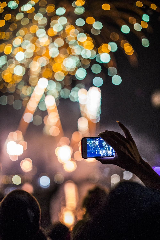 person holding smartphone capturing fireworks