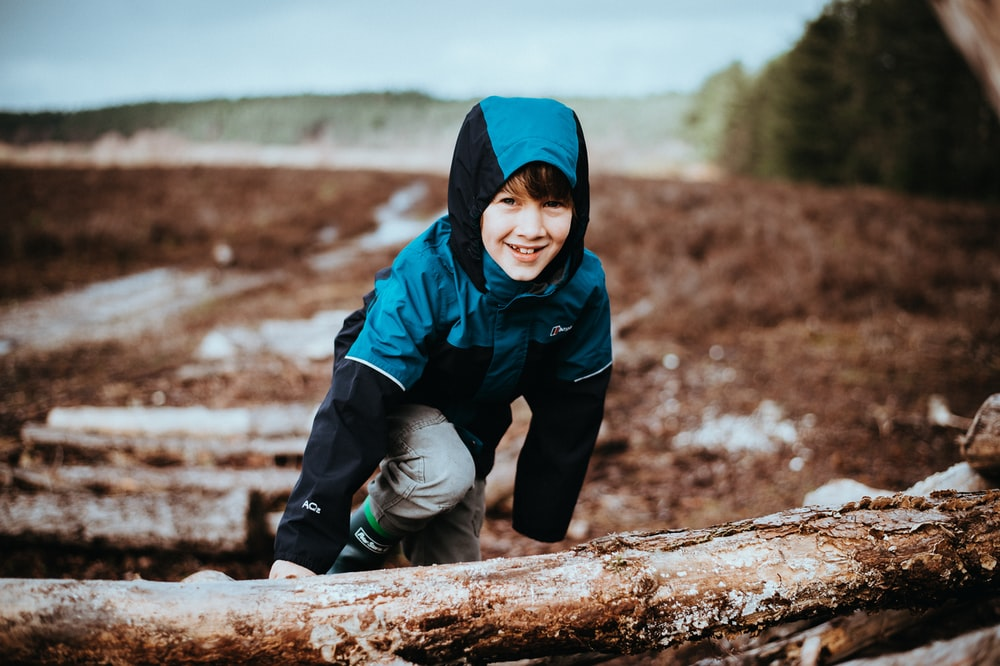 boy climbing on tree stump