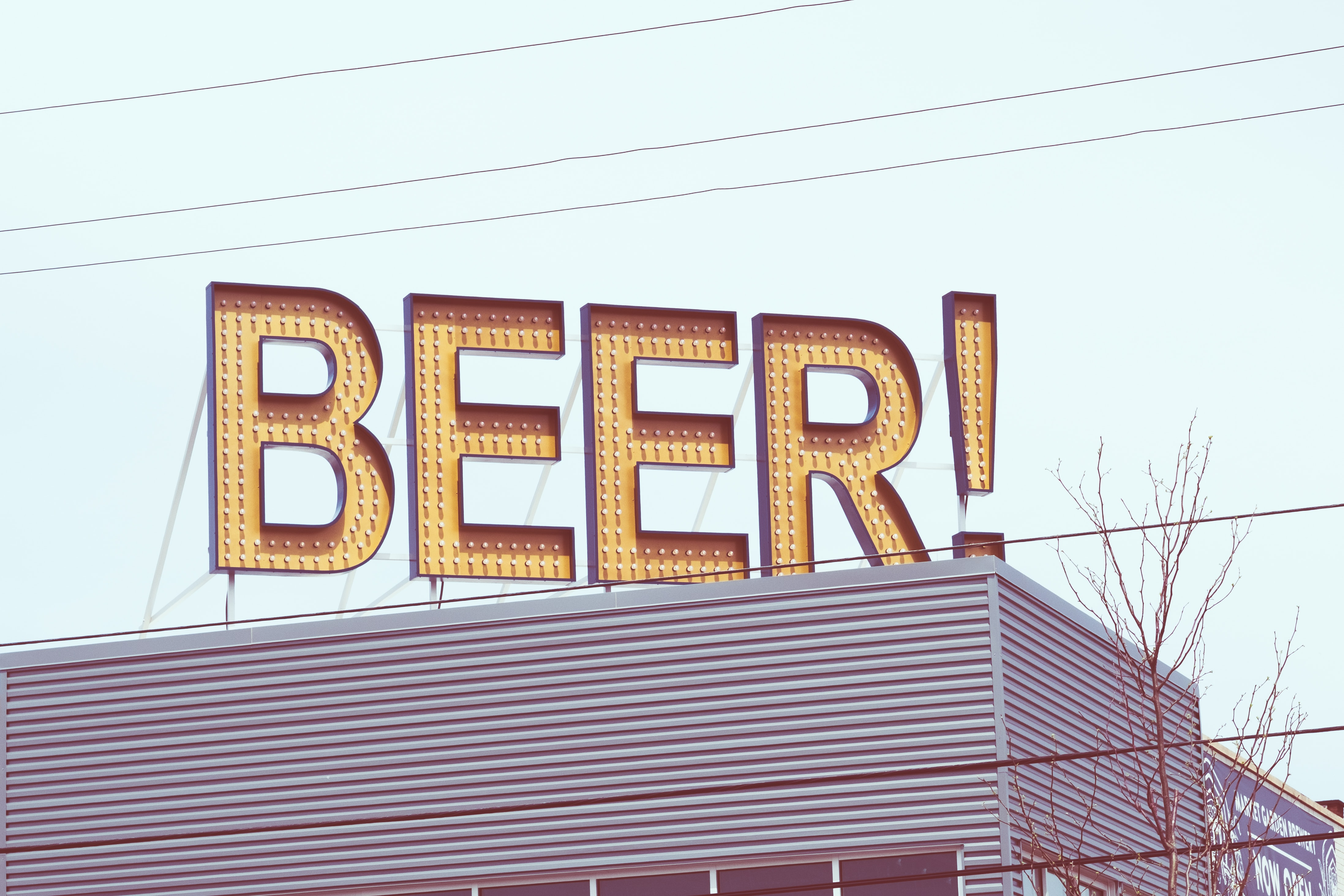 A beer sign with small lights on it on a bar
