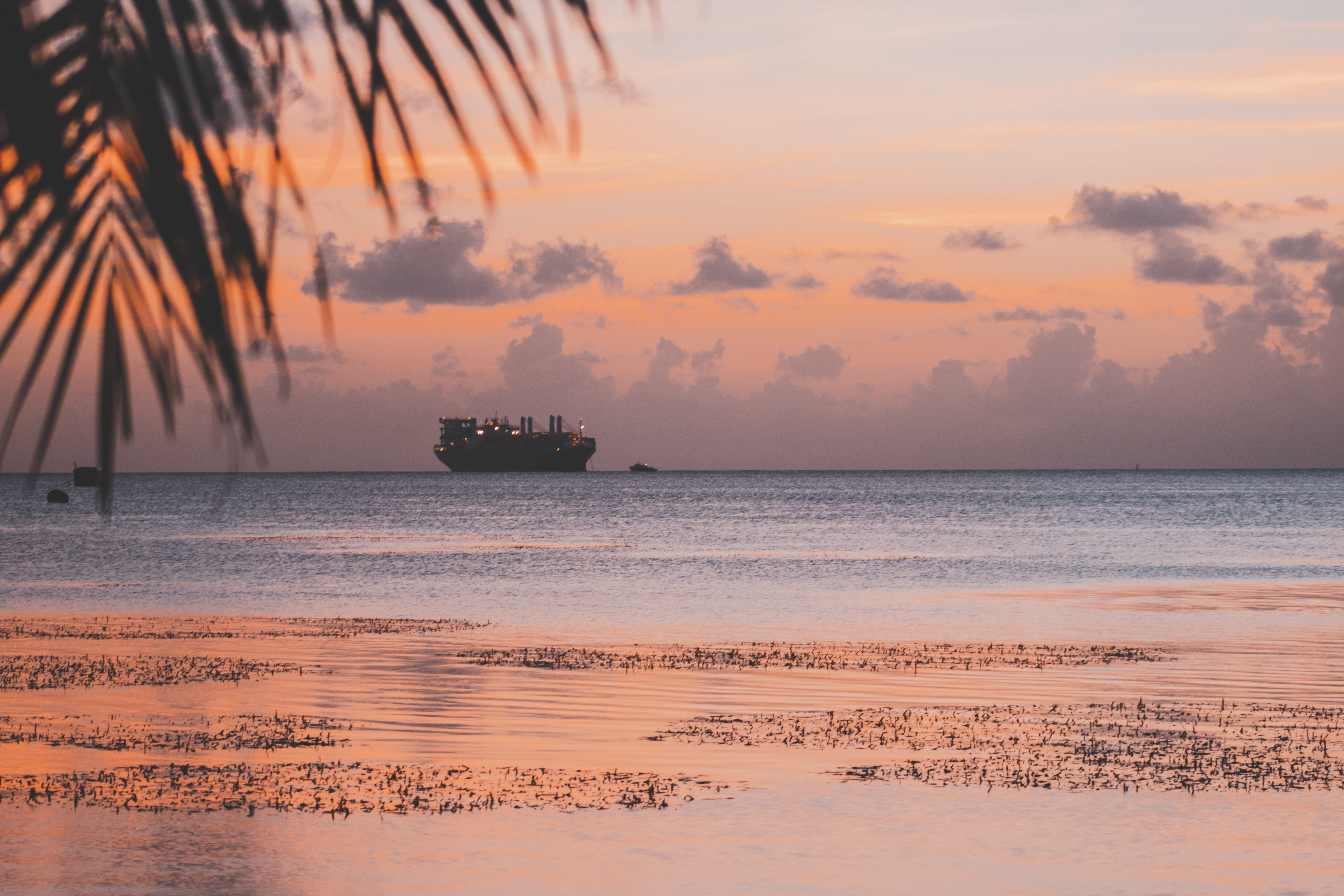 Large ship silhouette on the horizon from a tropical beach in Saipan at sunset