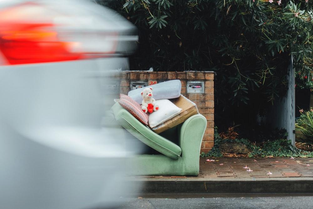 white bear plush on sofa chair beside road