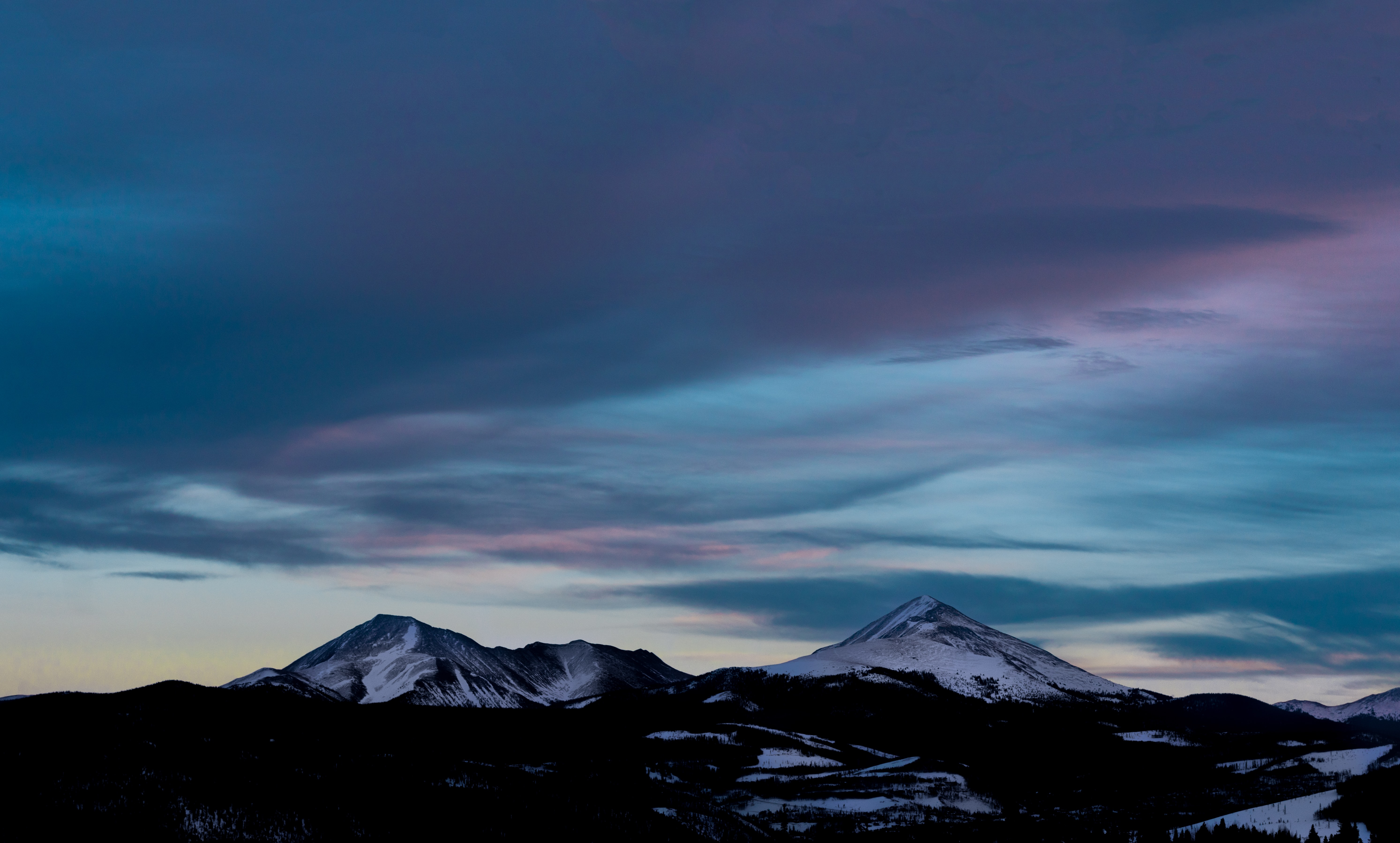 A mountain peak rising up against the cloudy evening sky in Silverthorne