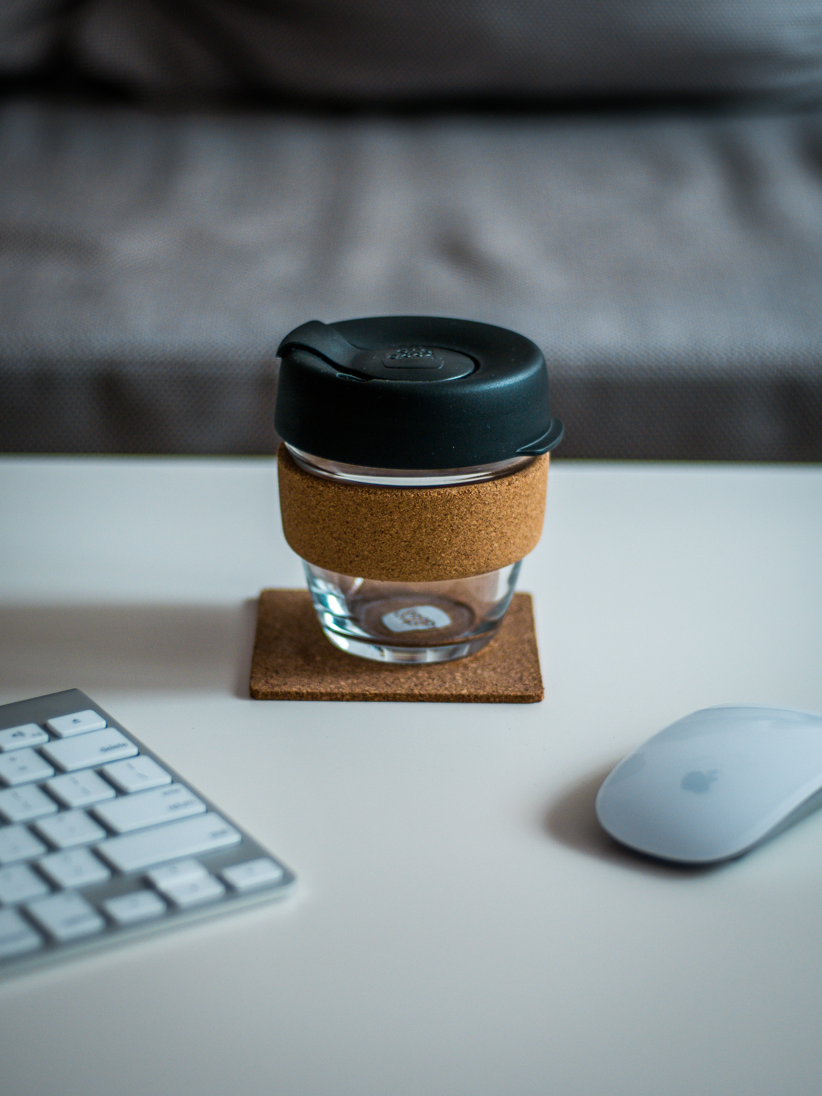 covered jar between Magic Mouse and Keyboard on desk