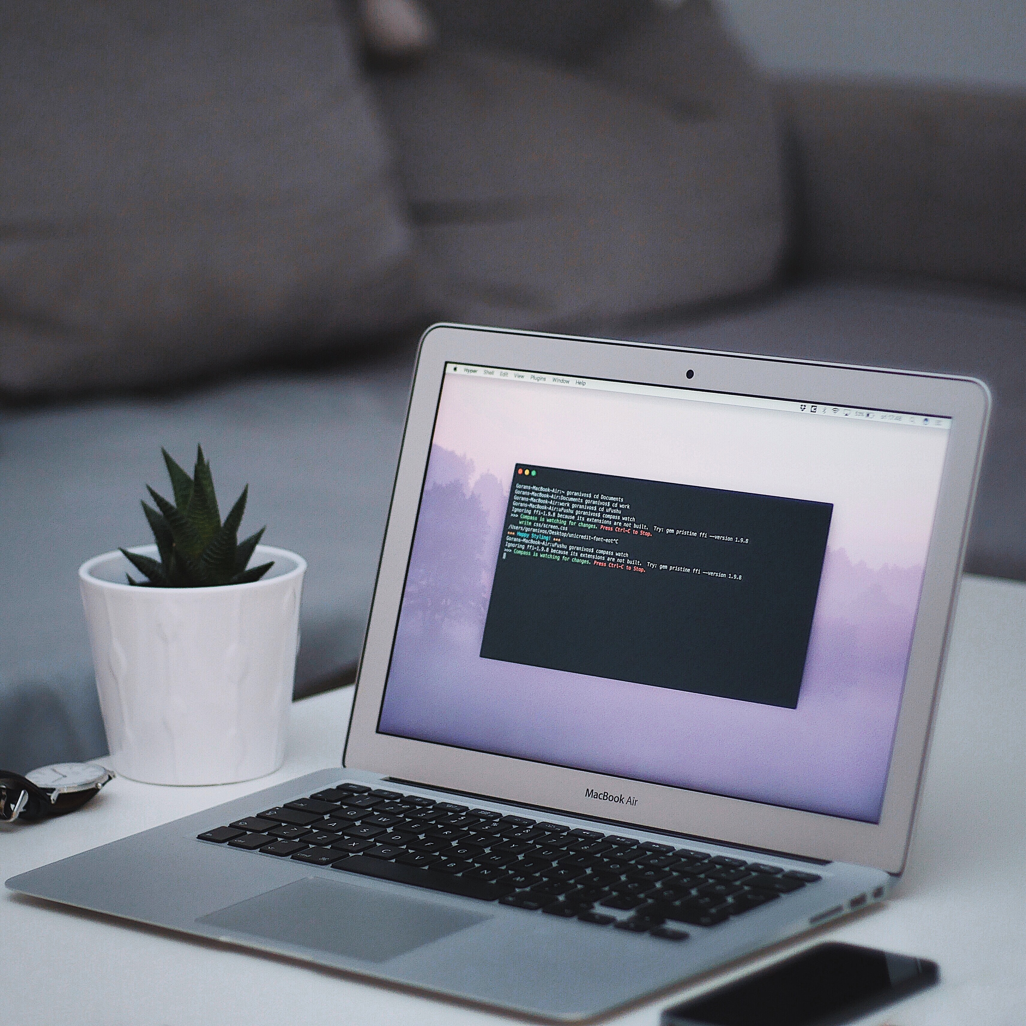 A MacBook with lines of code on its screen