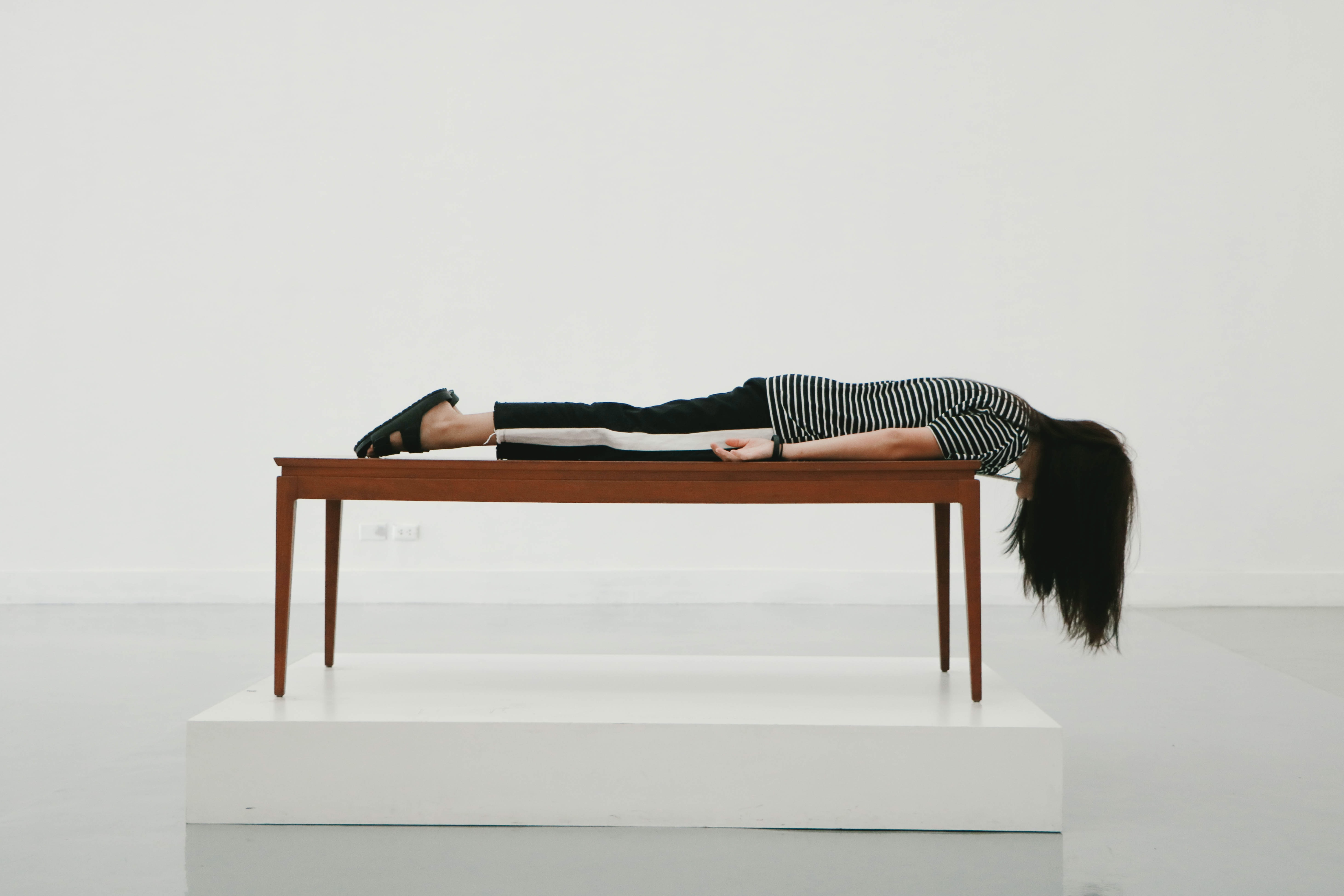 Lady at the Bangkok Art and Culture Centre lays on stomach on a wood table