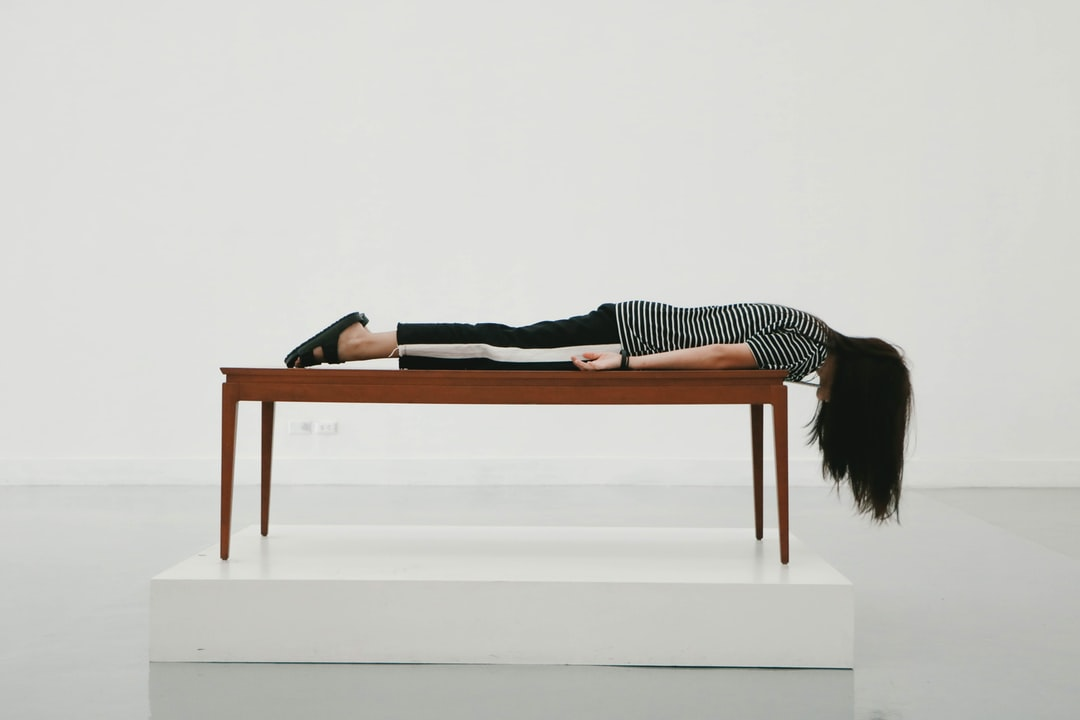 A woman lies face down on a table