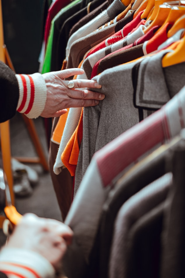 A shopper browsing clothing hung up on a rack.
