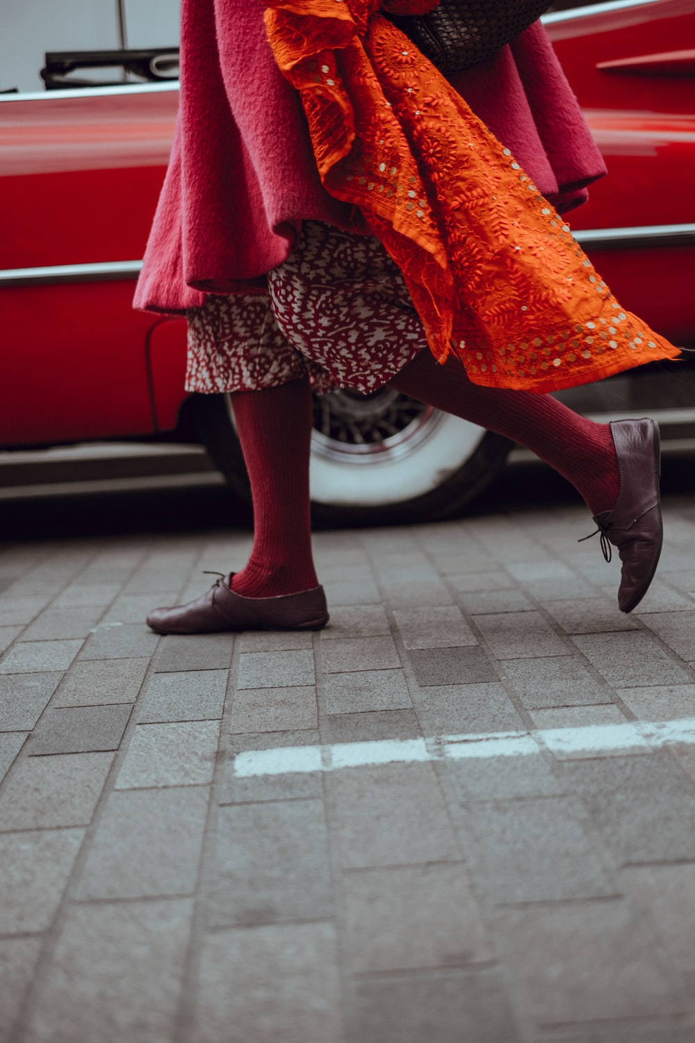 photo of person walking in front of red vehicle