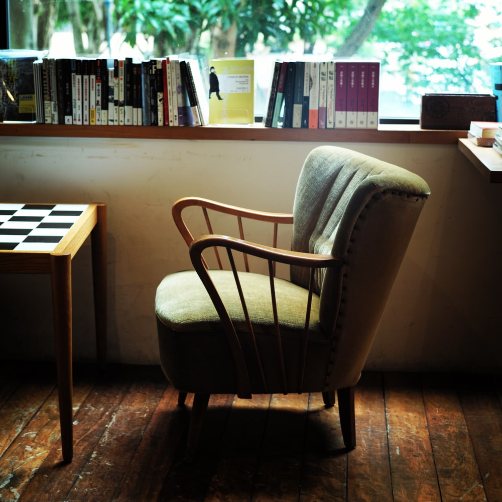 An armchair, checkered table, and books in a room with wooden floorboards